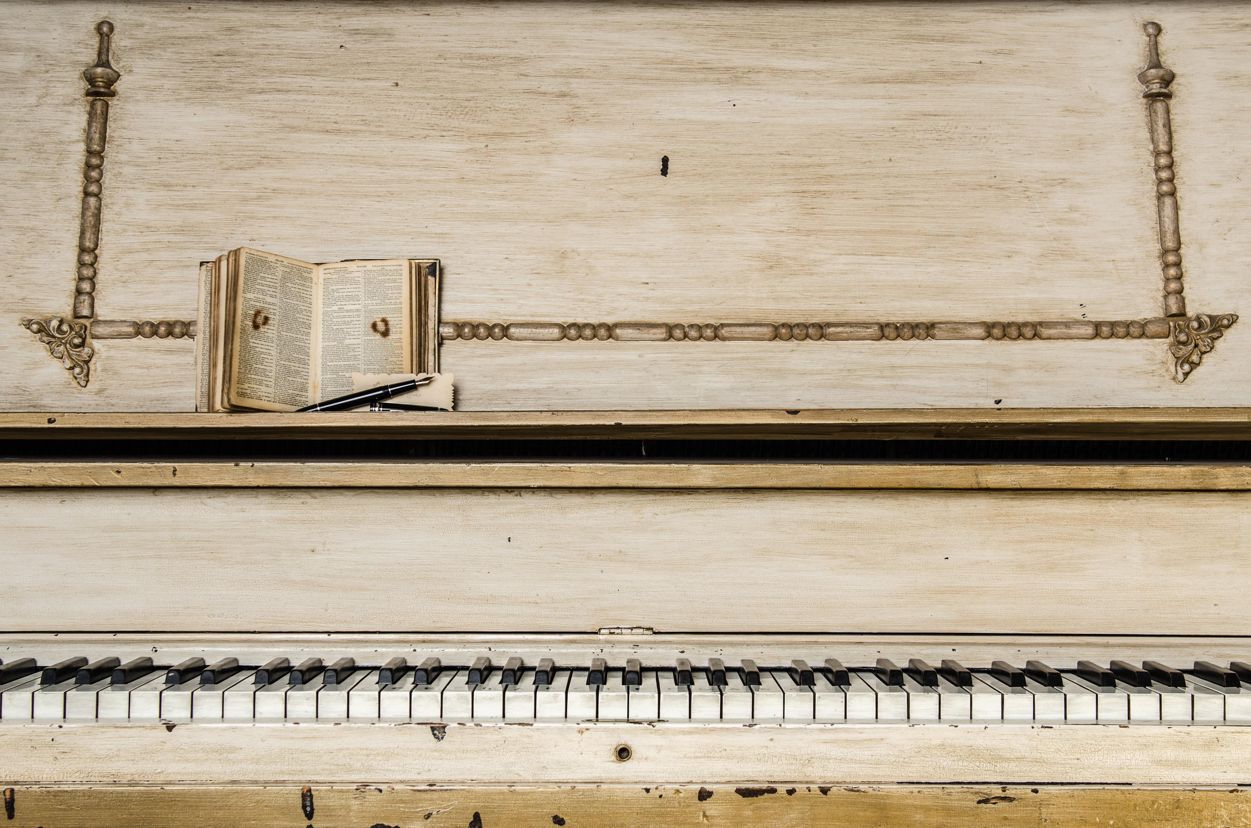 A worn-out beige piano with a little booklet and a pen on it