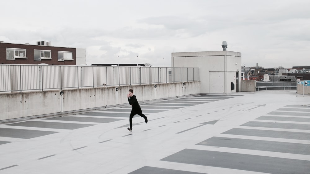 person running on concrete lot during daytime