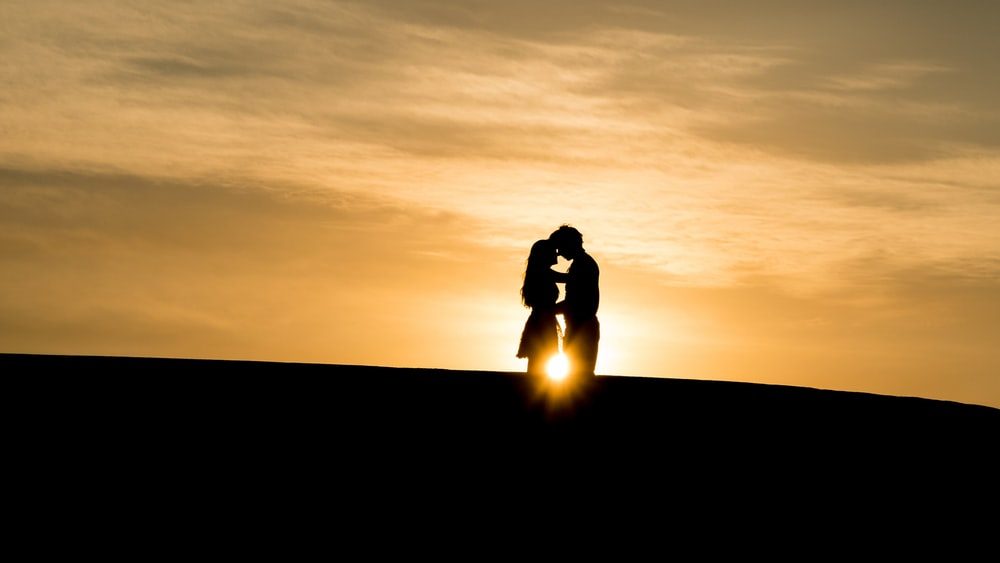 man and woman's silhouette on hill during golden hour