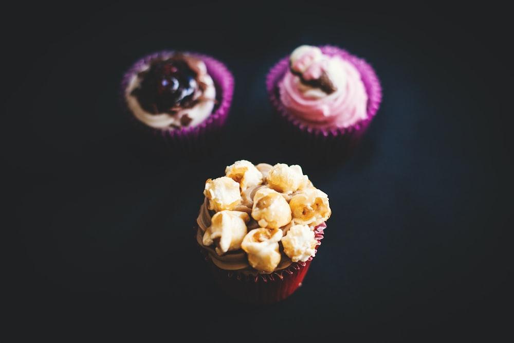 three closeup photography of three cupcakes