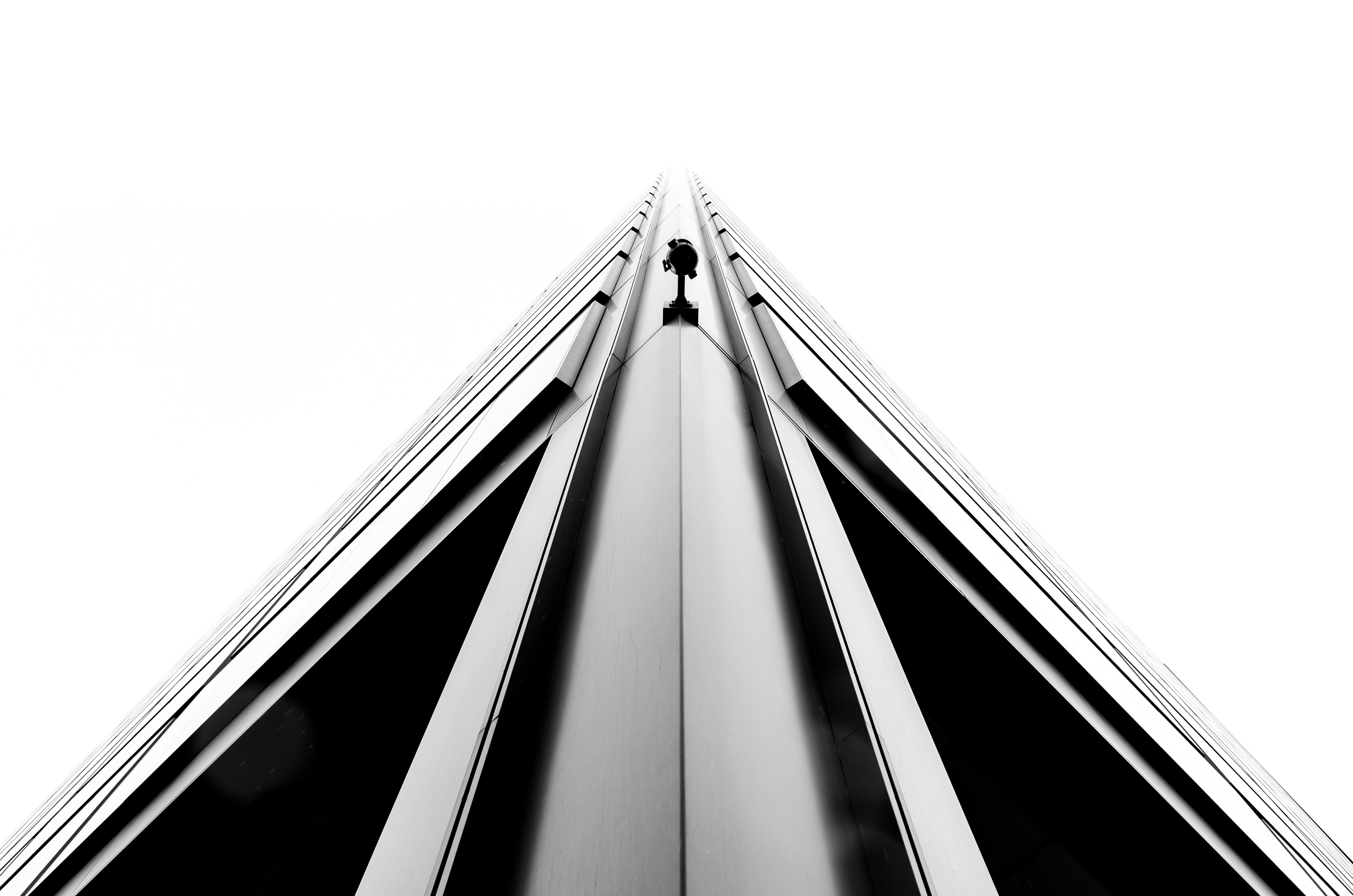A monochrome shot of a sharp edge on a corner of a tall building