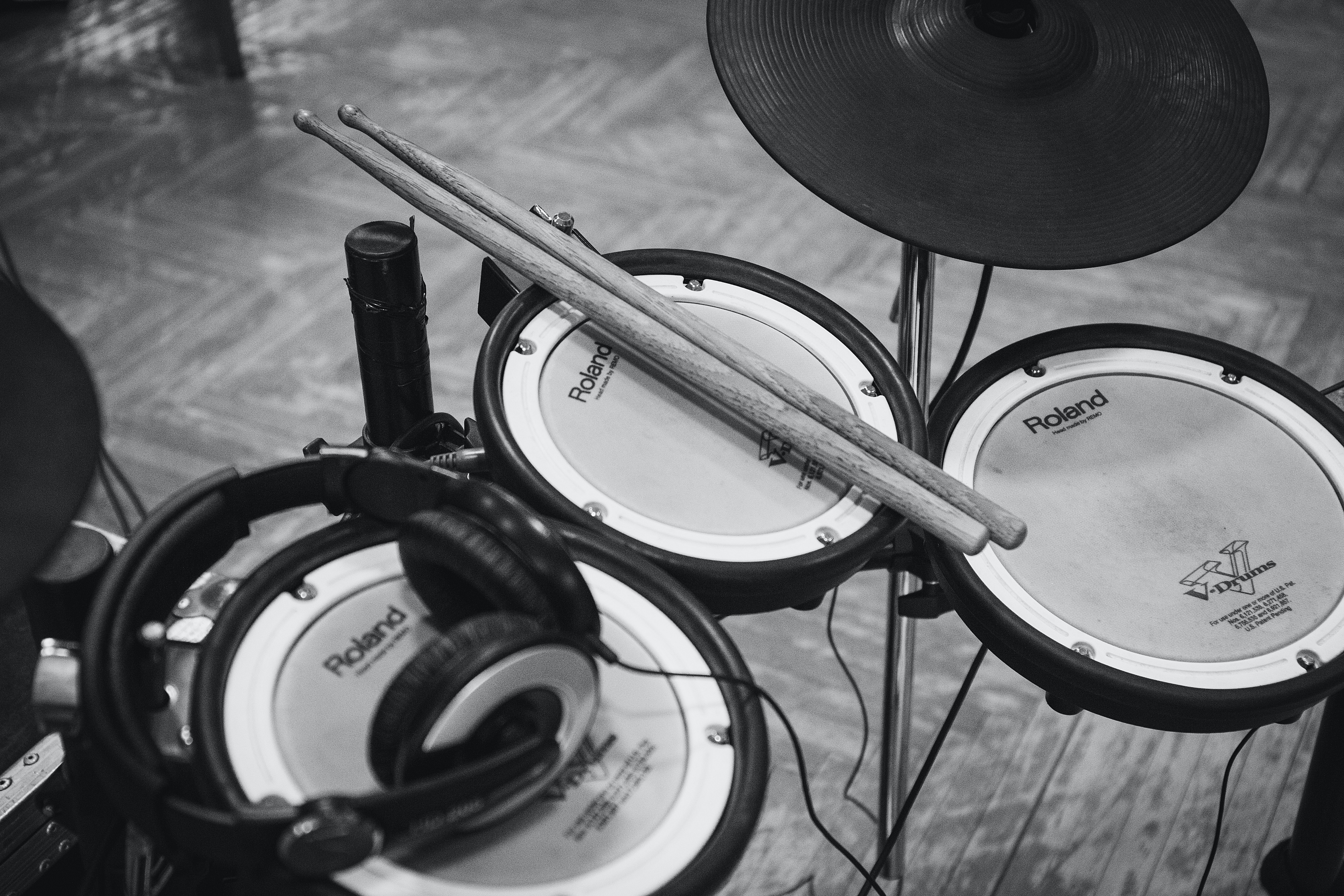 A black-and-white shot of a Roland drumset with headphones and drumsticks