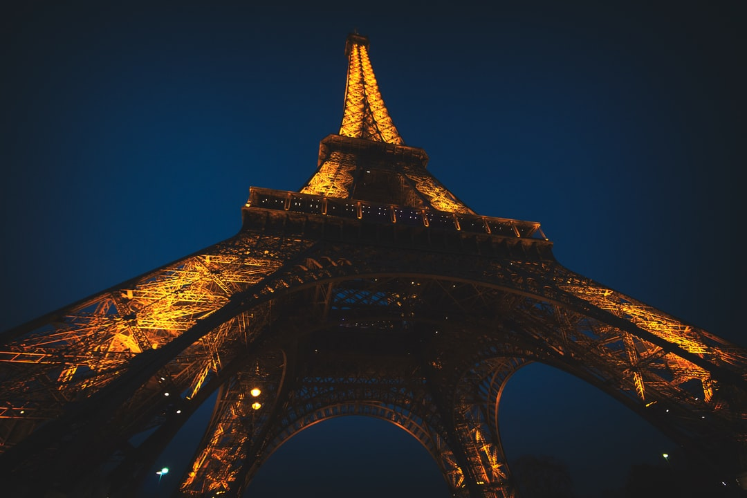 Looking up at the Eiffel Tower illuminated at night in Paris