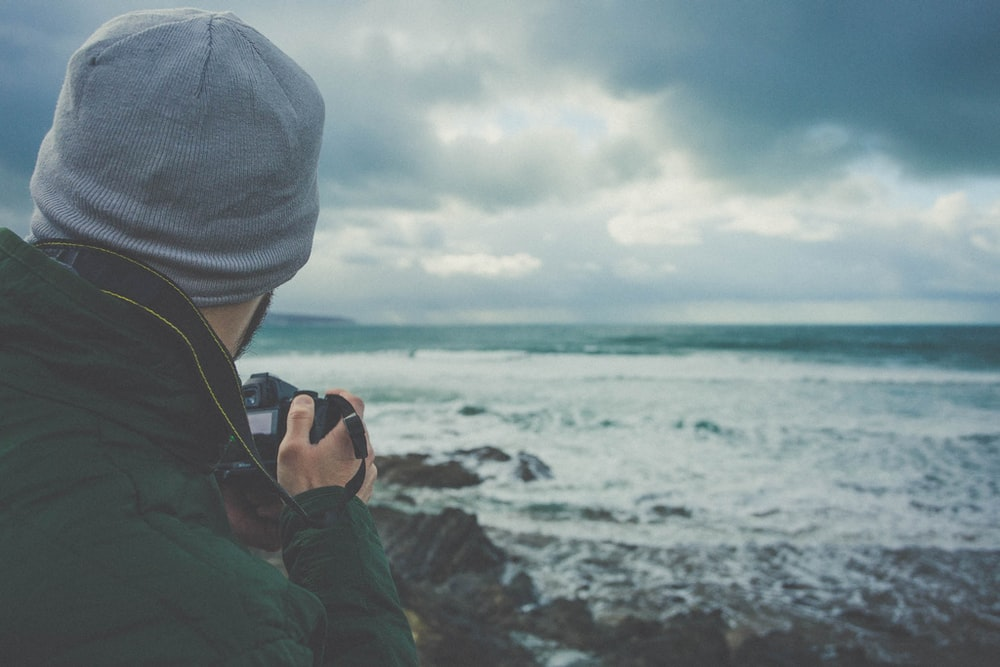 man holding DSLR camera taking picture of beach waves