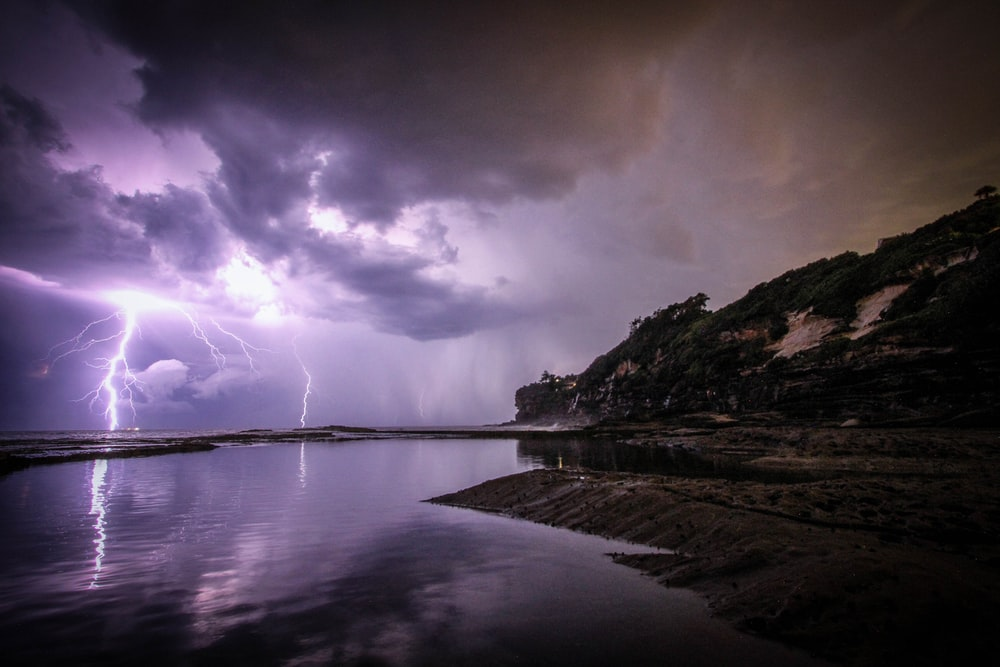 lightning near body of water and rock formation