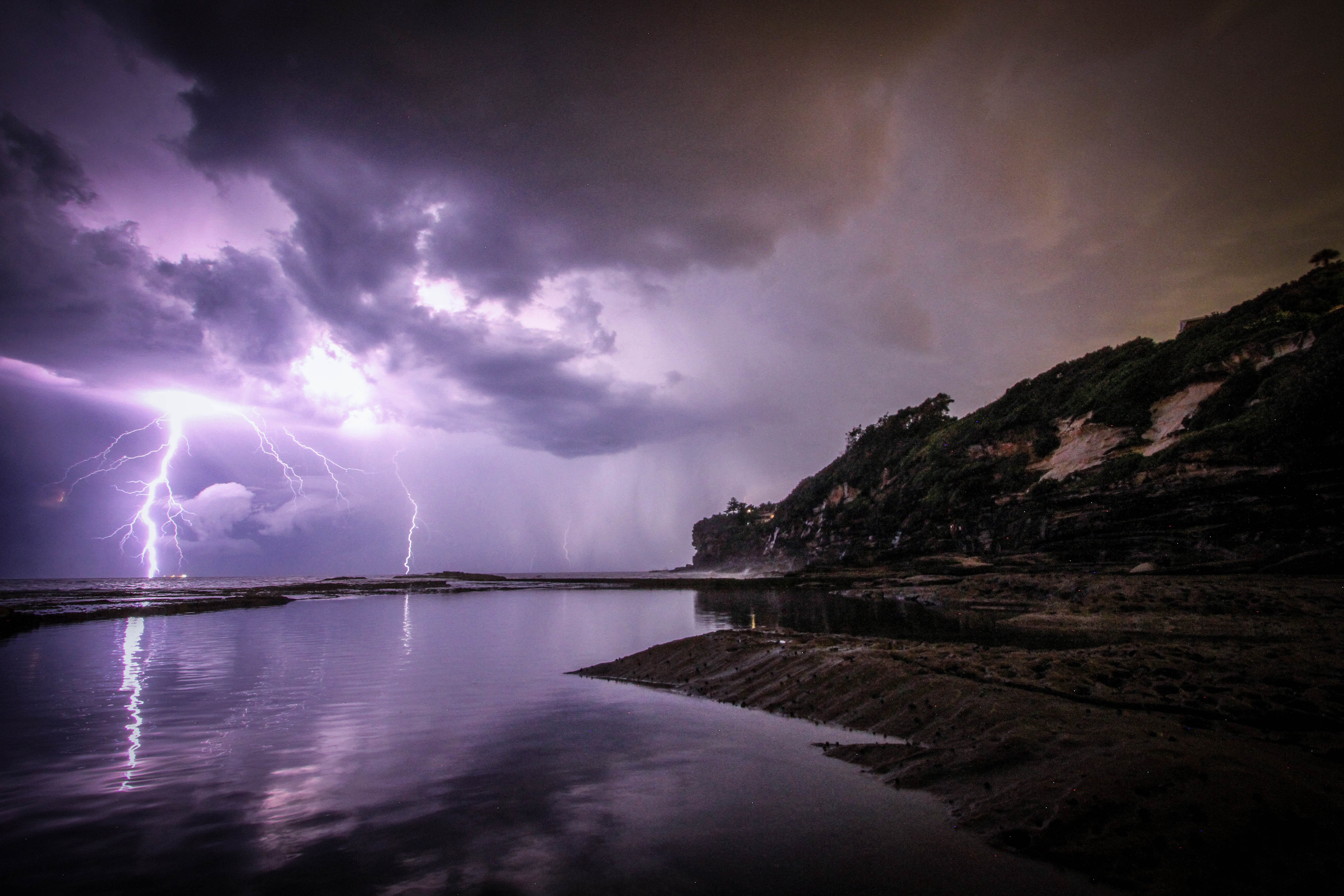 Purple lightning streaks at sea as seen from the coast in Dee Why.