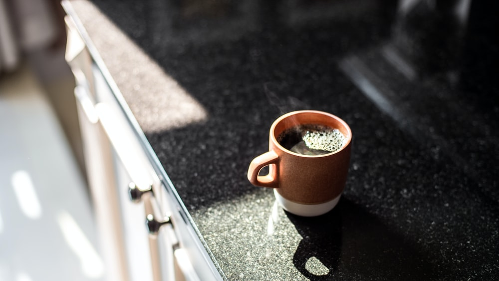 brown and white ceramic mug on table