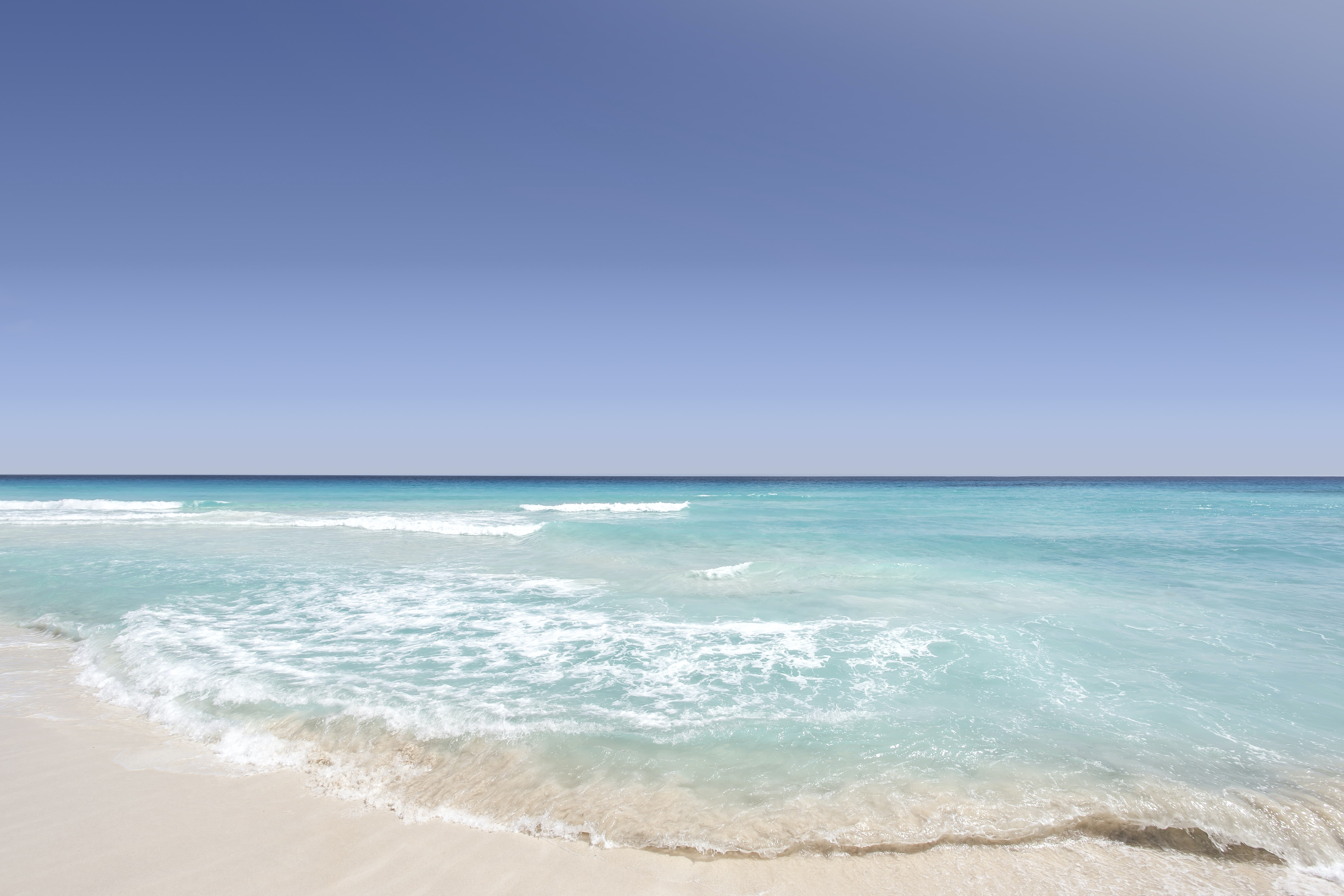 Clear blue ocean washing on the sandy shore on a clear day in Cancún