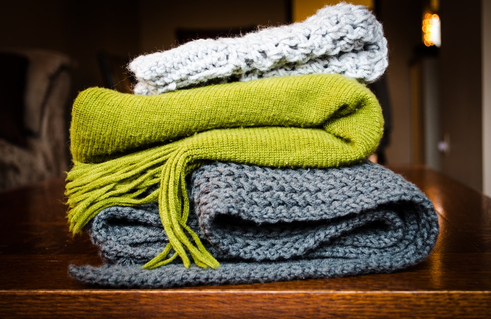 three gray, green, and white scarf on top of table