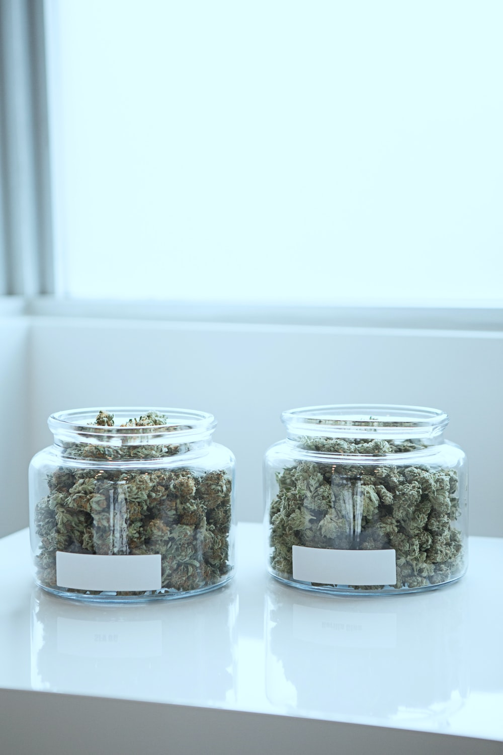full of kush in clear glass jars on table