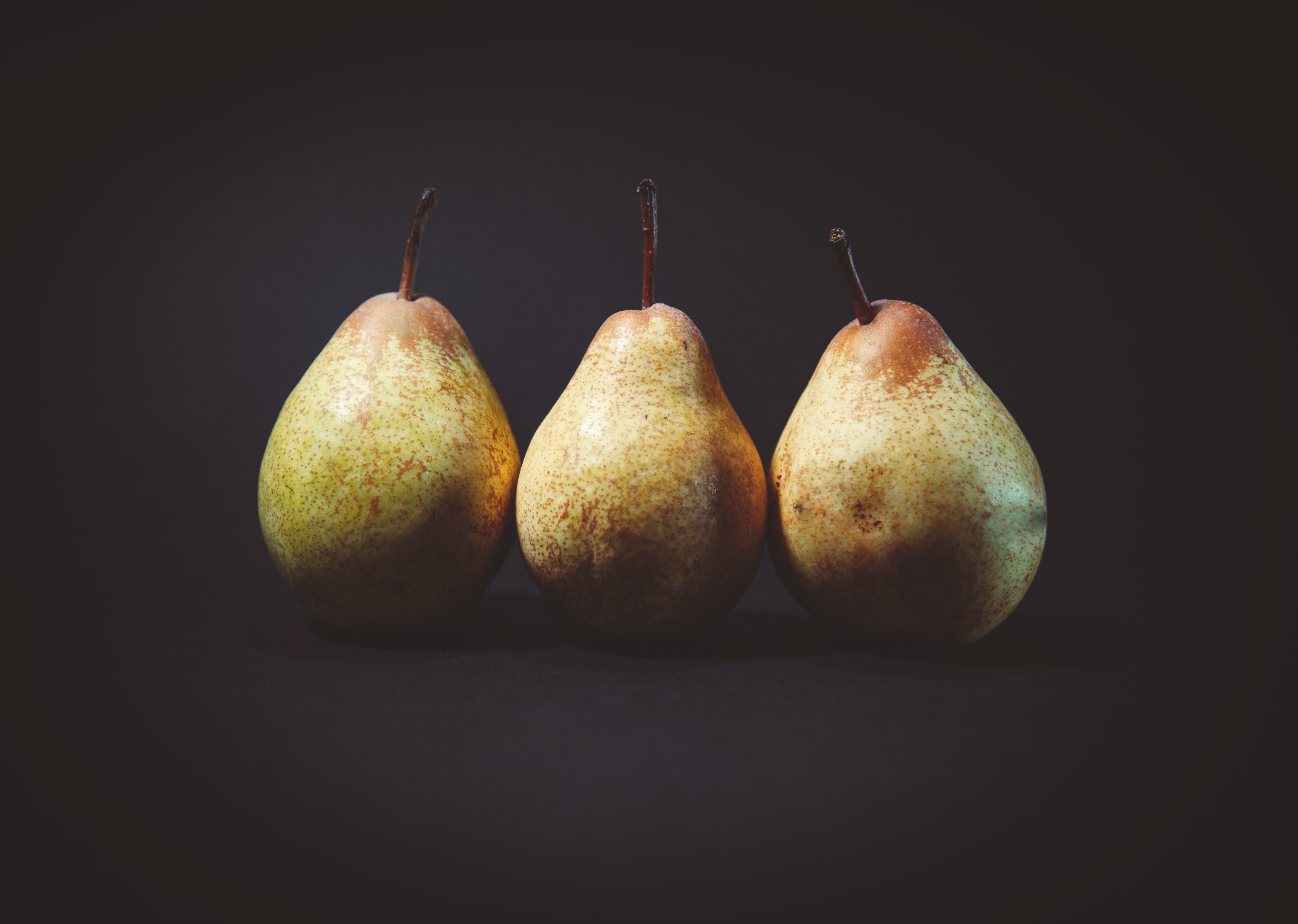 Three pears in a row against a black background