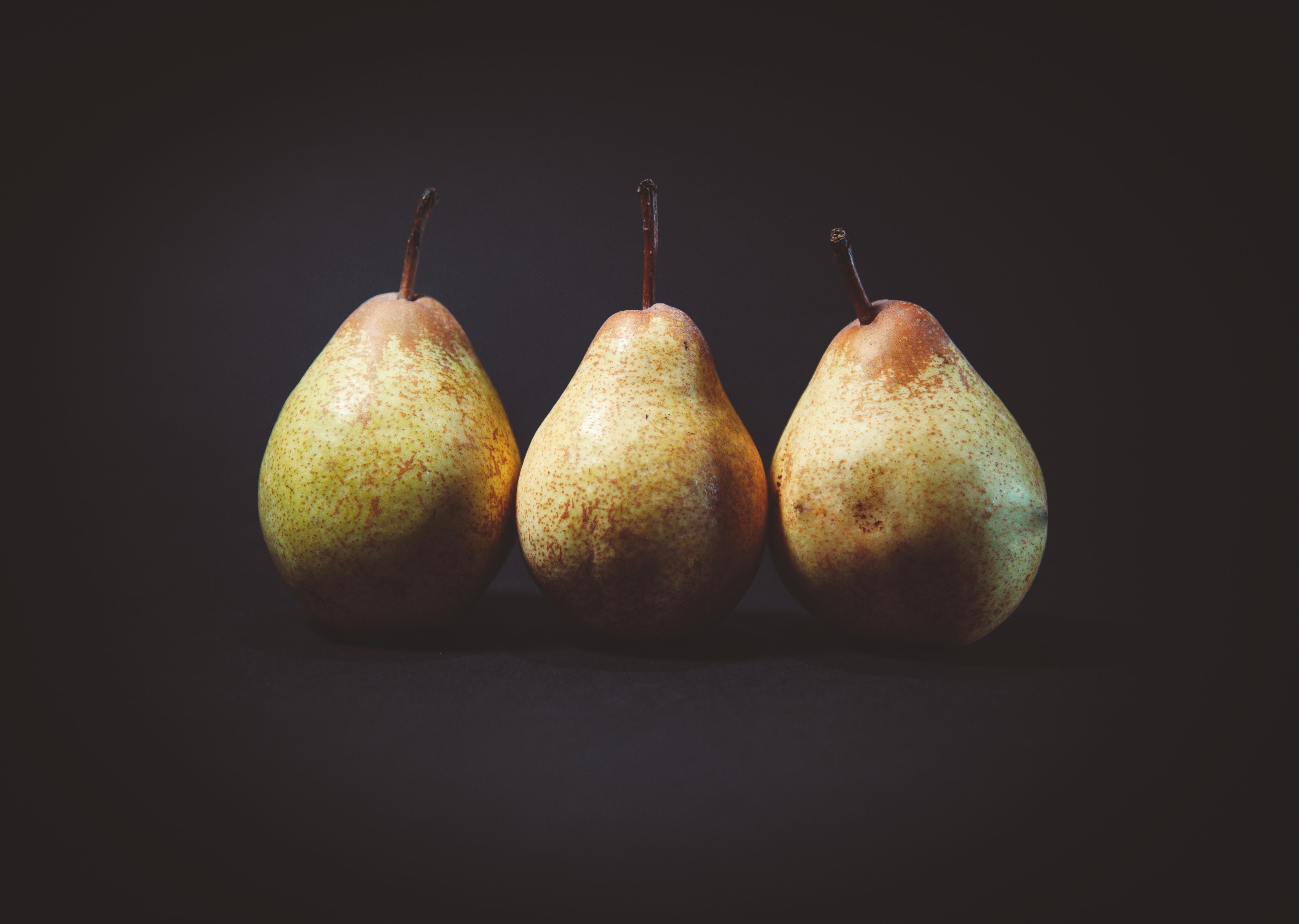 three pears on black surface