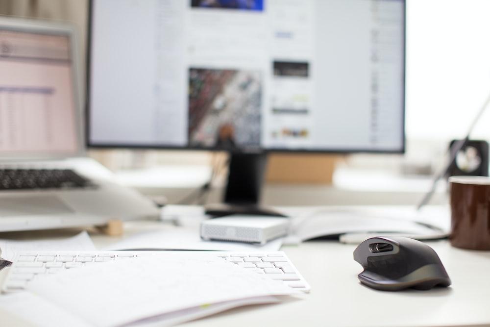 黒いフラットスクリーンコンピュータモニタと灰色のワイヤレスマウス