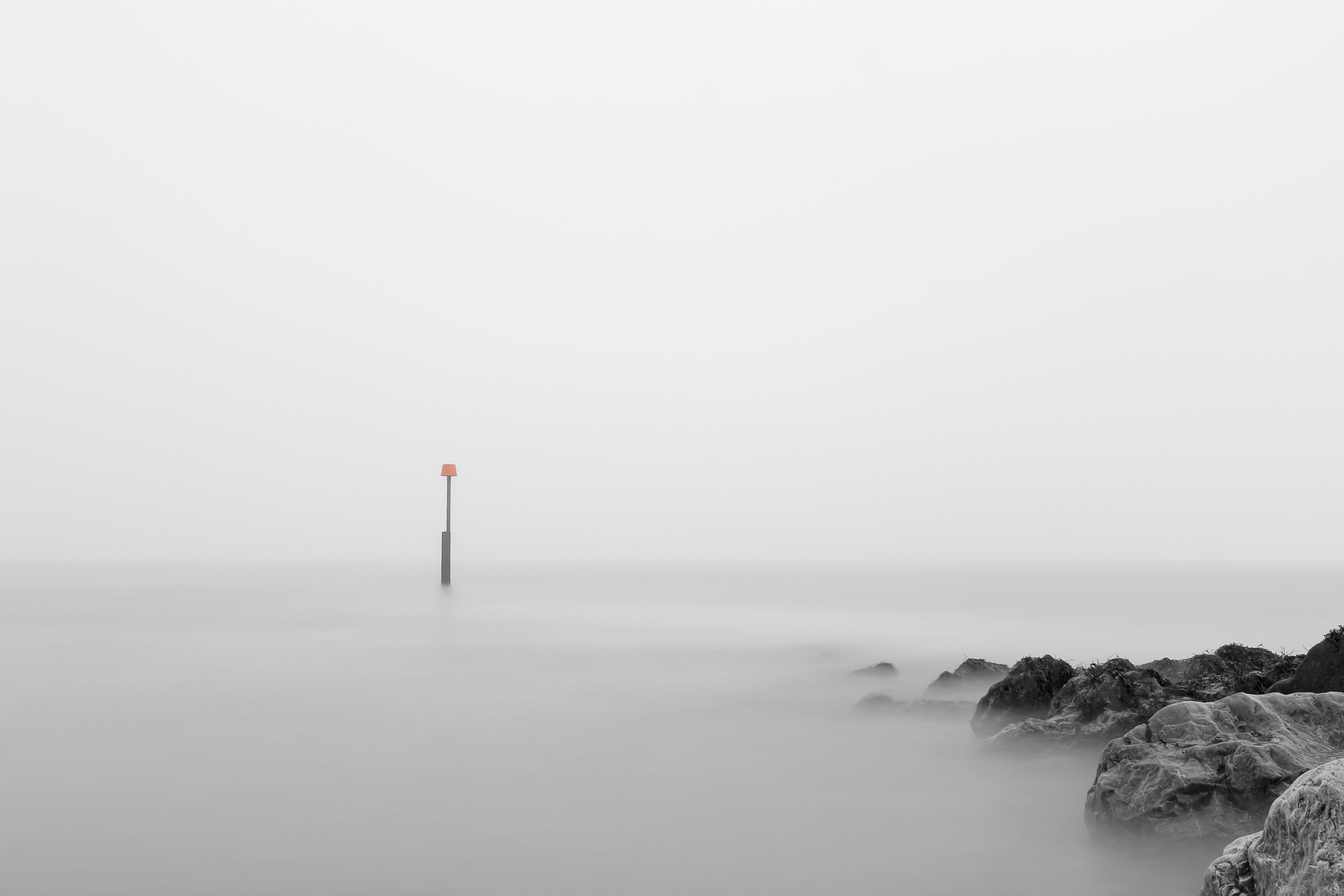Isolated sign in the middle of a foggy sea near rocks