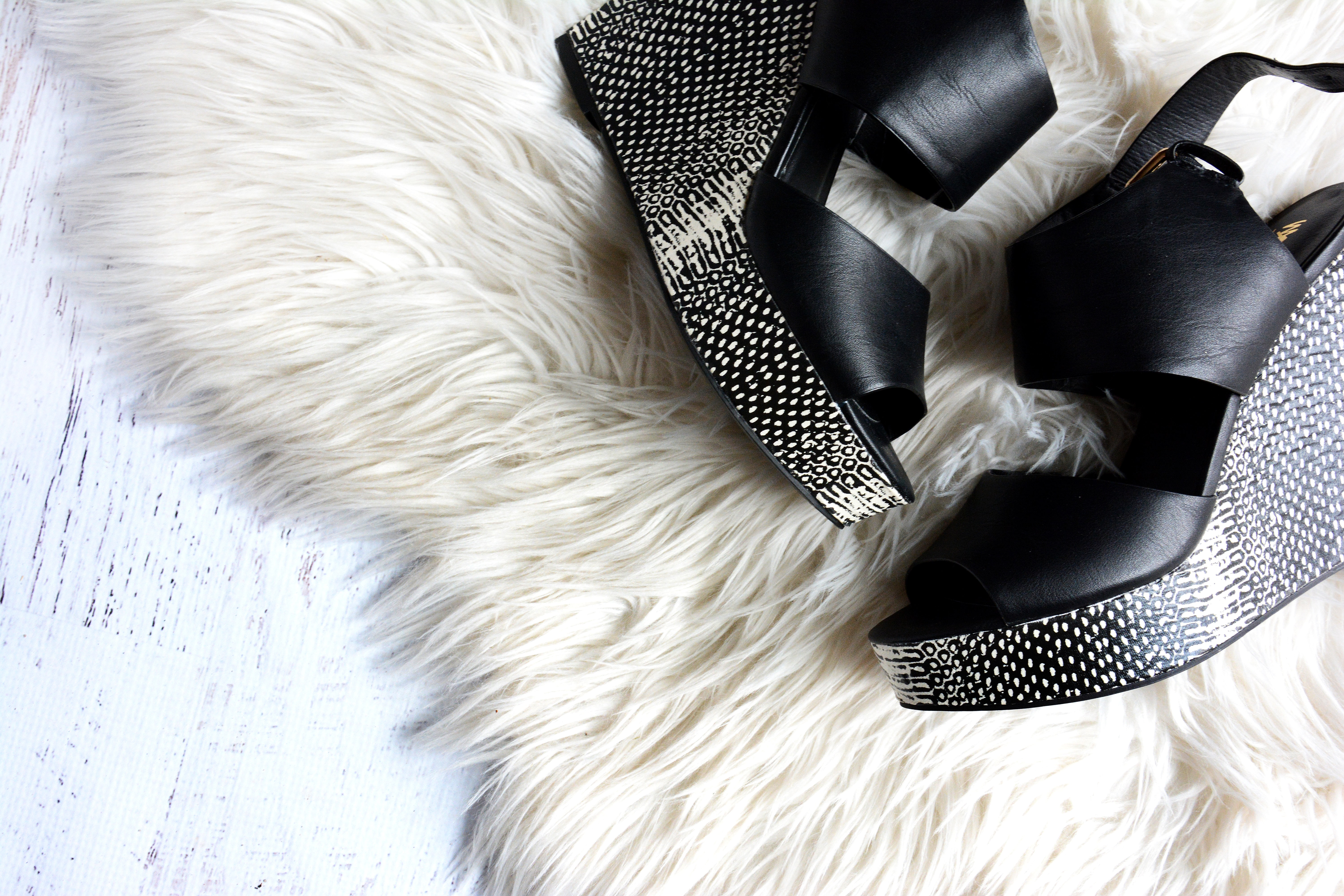 pair of women's black-and-gray wedges on white fur textile