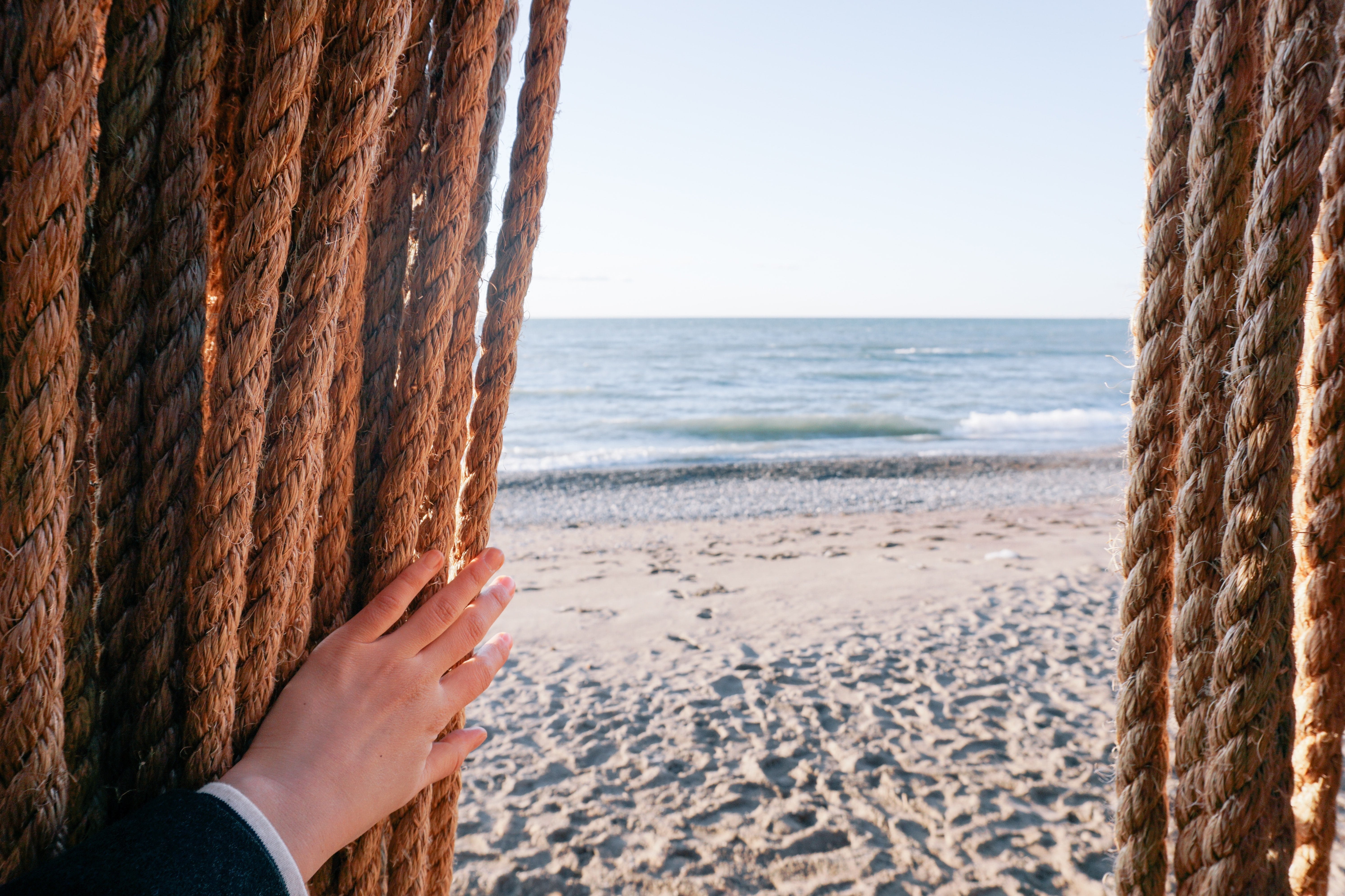 A person's hands pushing long hanging ropes aside on a sandy beach