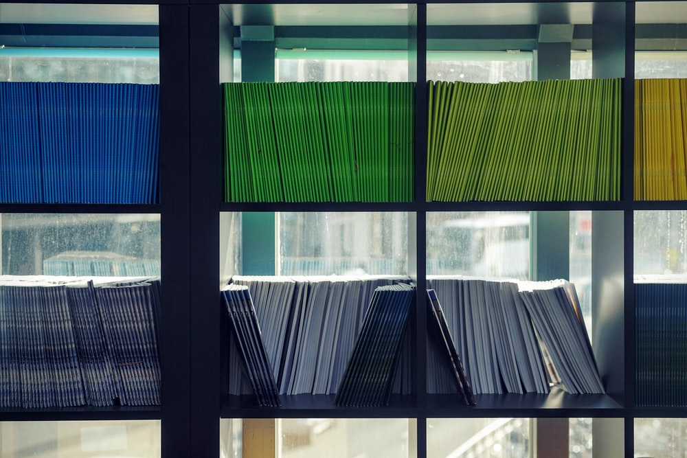 Books with uniform colorful covers on bookshelves in a library