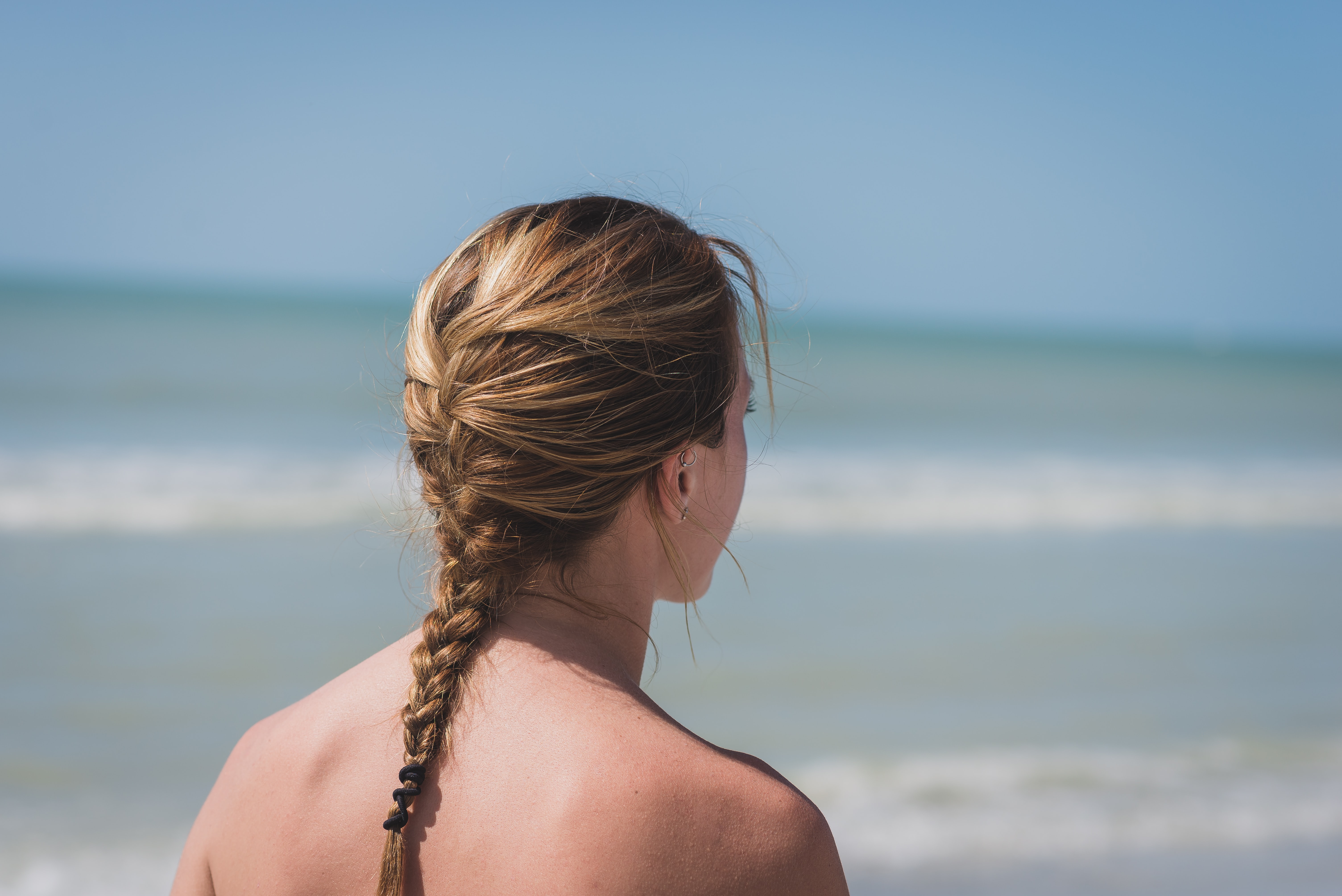 back view photo of woman with braided hair near sea