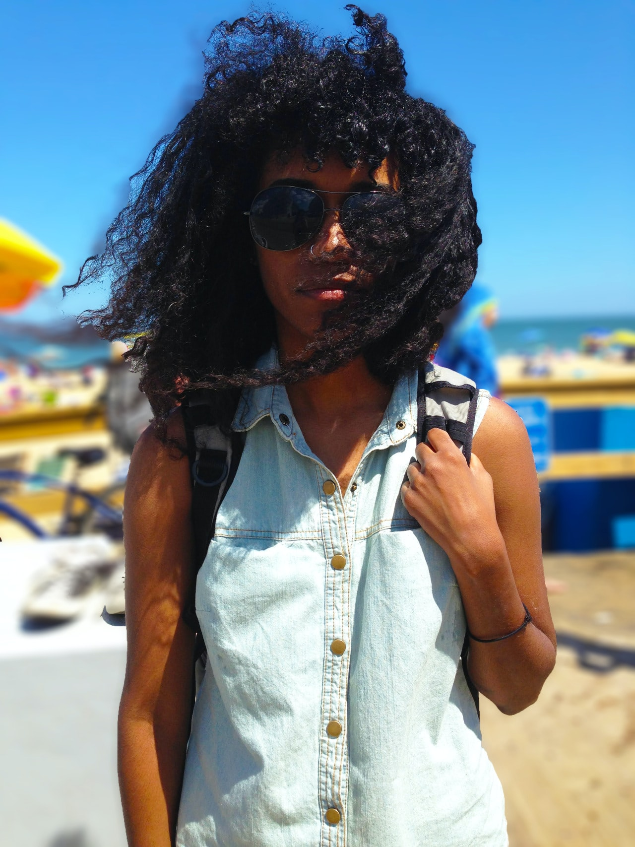 Woman with curly hair, sunglasses, and a jean shirt on a beach in Ocean City, Maryland