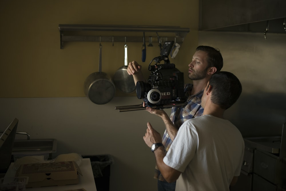 two men fixing camera inside kitchen