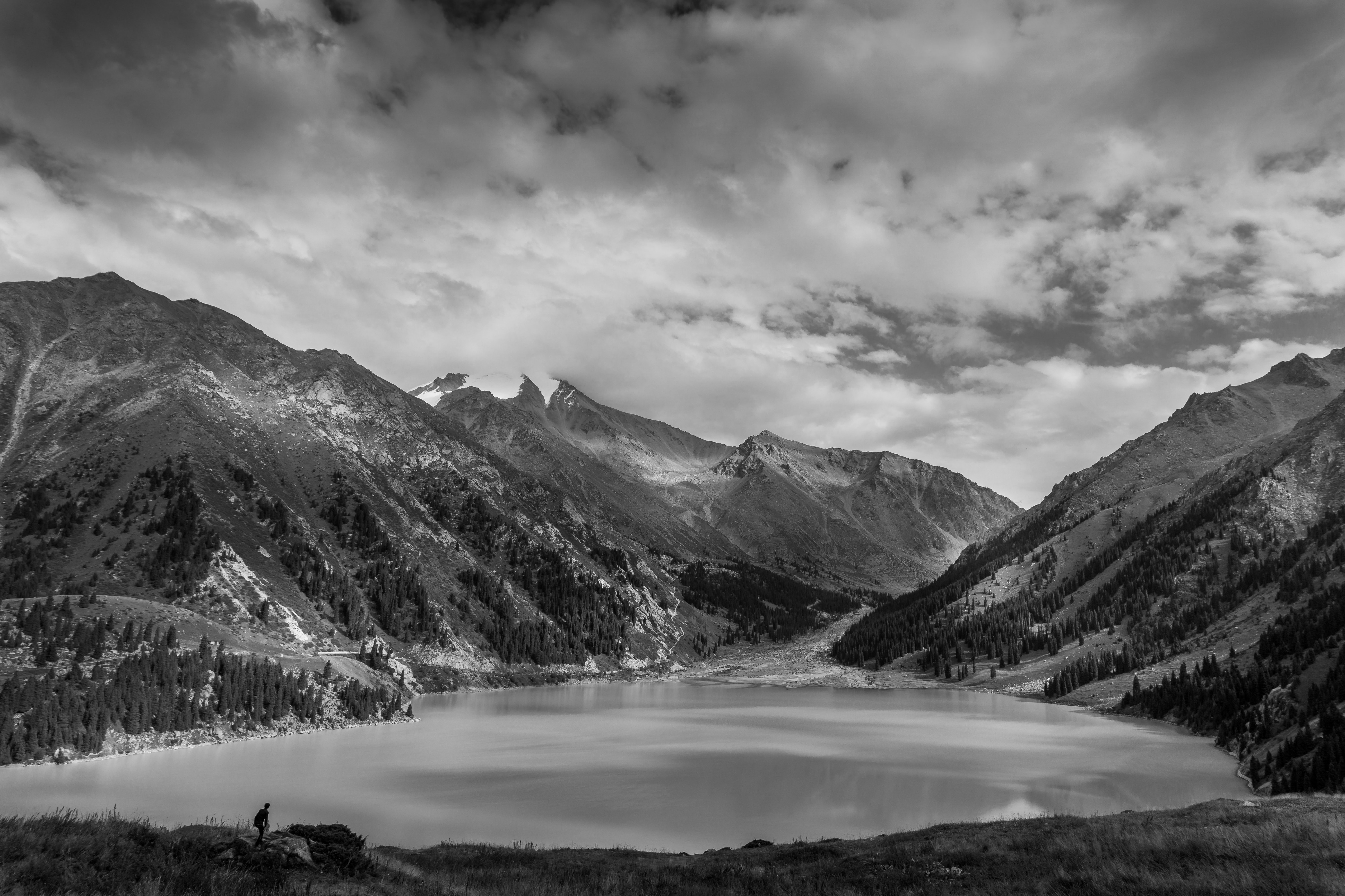 Black and white shot of beautiful mountain lake with cloudy sky in Kazakhstan