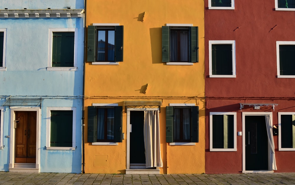 minimalist photography of open doors and windows of colored buildings