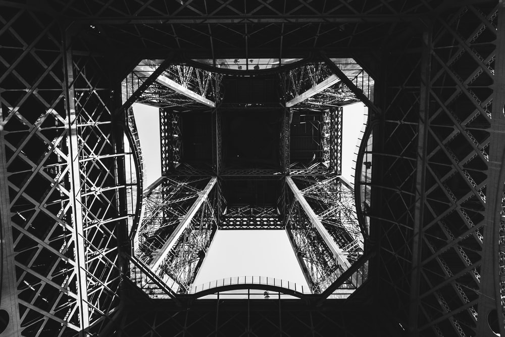 A dark photo looking directly up the Eiffel Tower from beneath it.