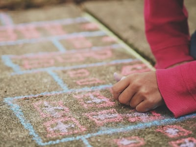 Child wearing red sleeves creates chalk art on sidewalk