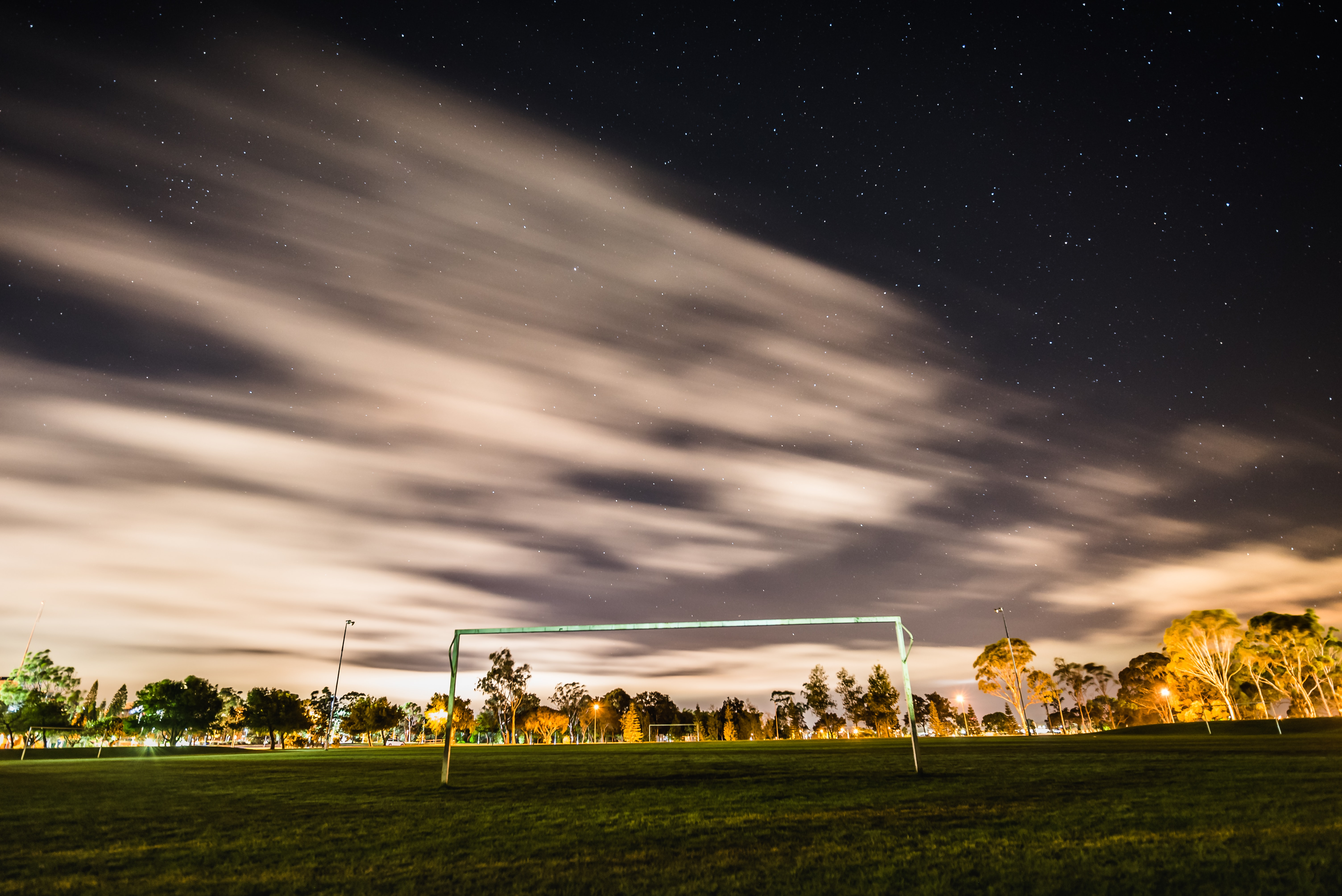 A soccer field at night with stars blurred in the sky