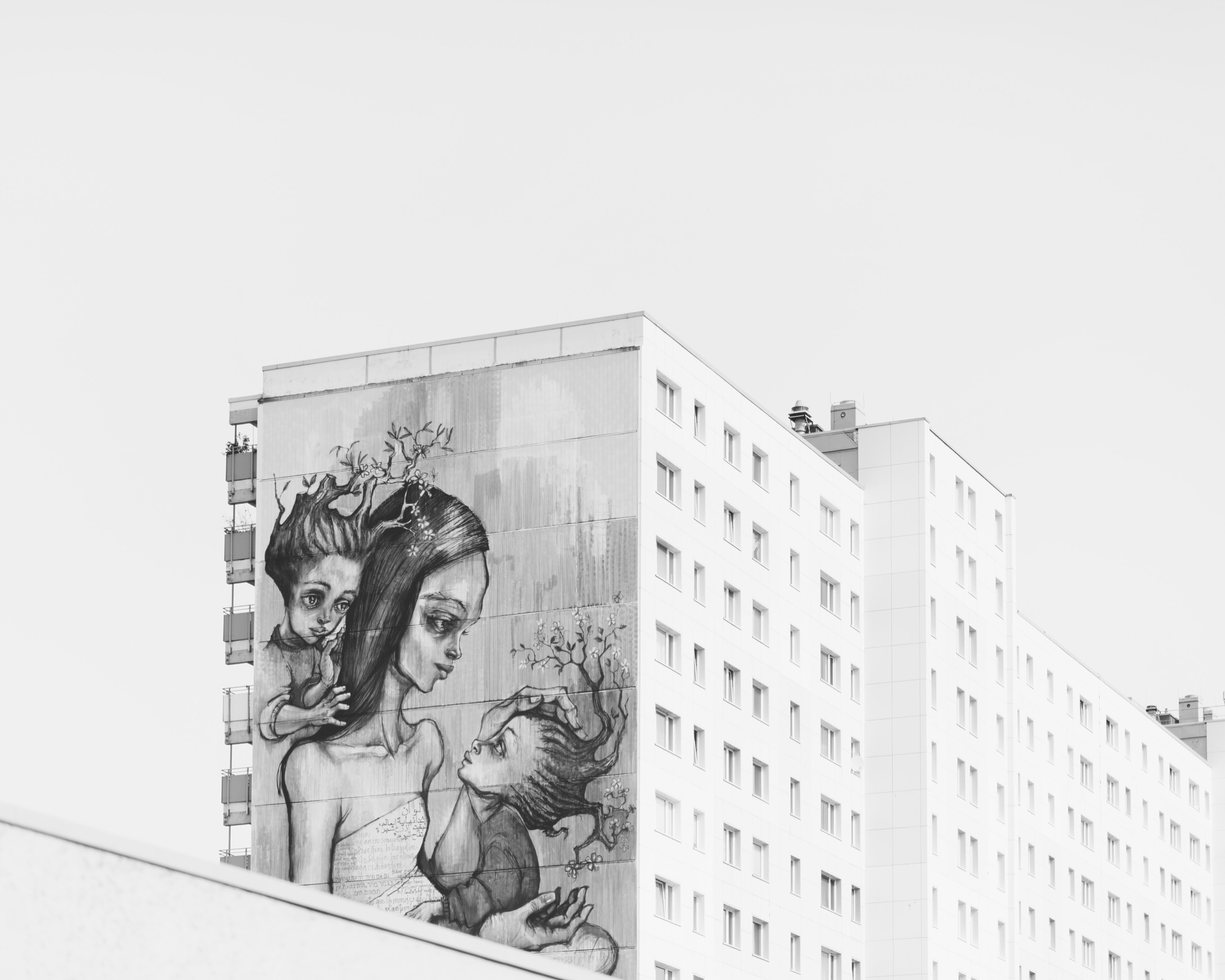 Black and white mural of exhausted mother with two children on side of building in Berlin