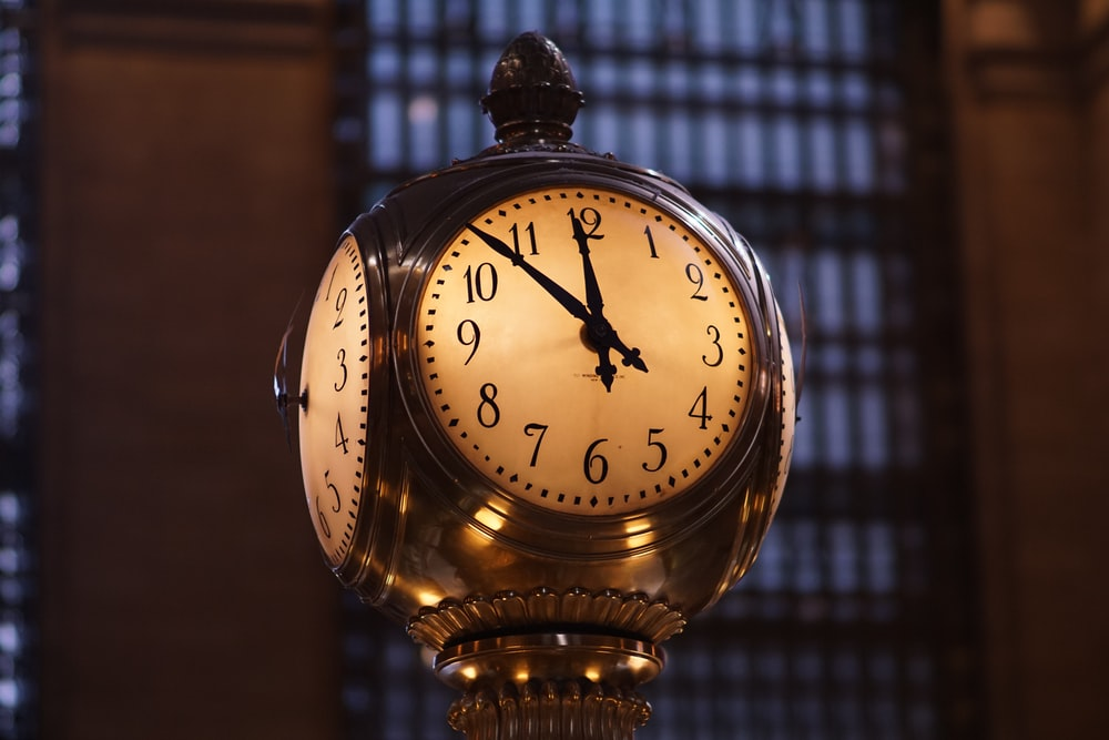turned on brass-colored train station analog clock