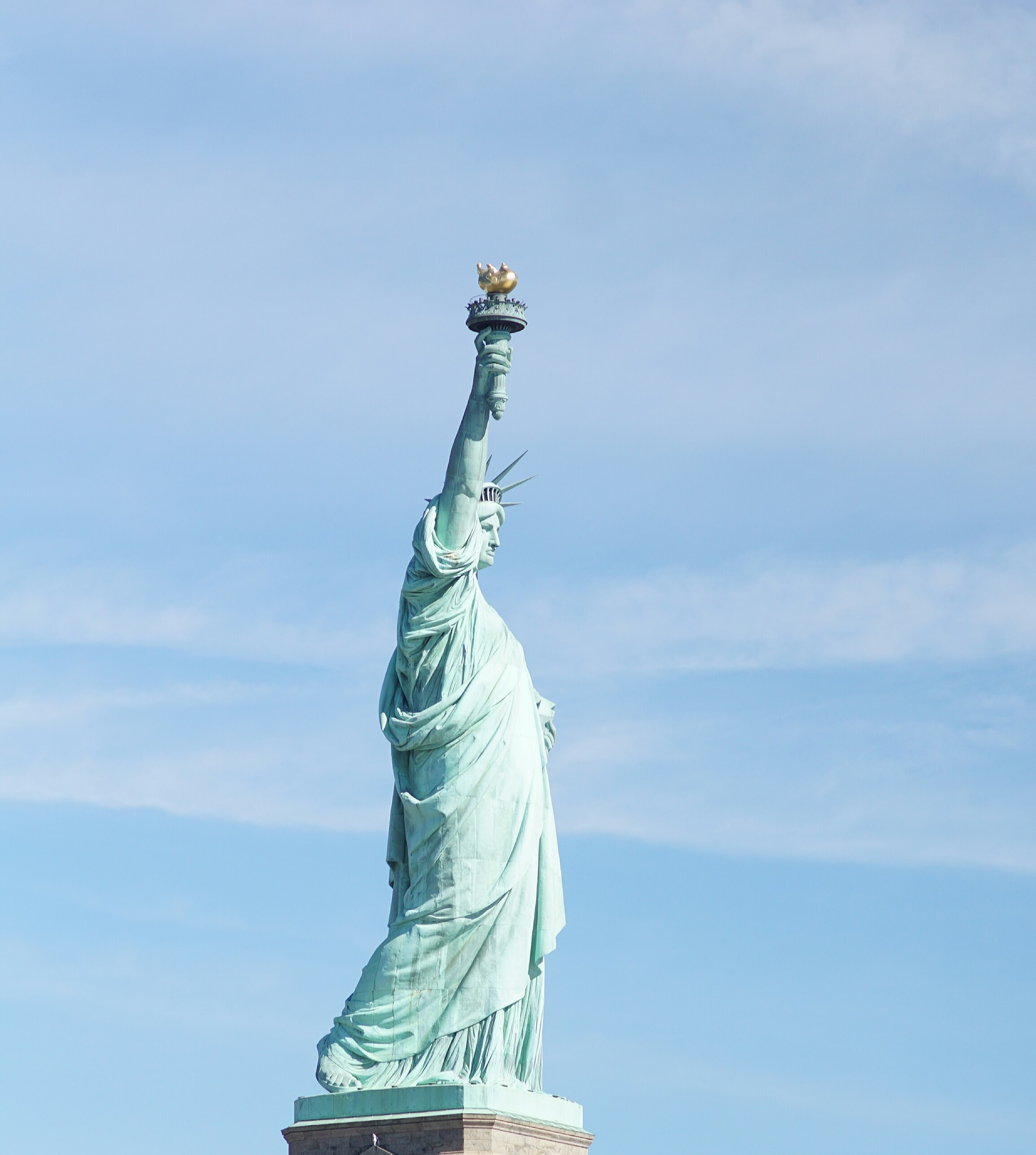 The Statue of Liberty stands tall against a bright blue sky in New York City