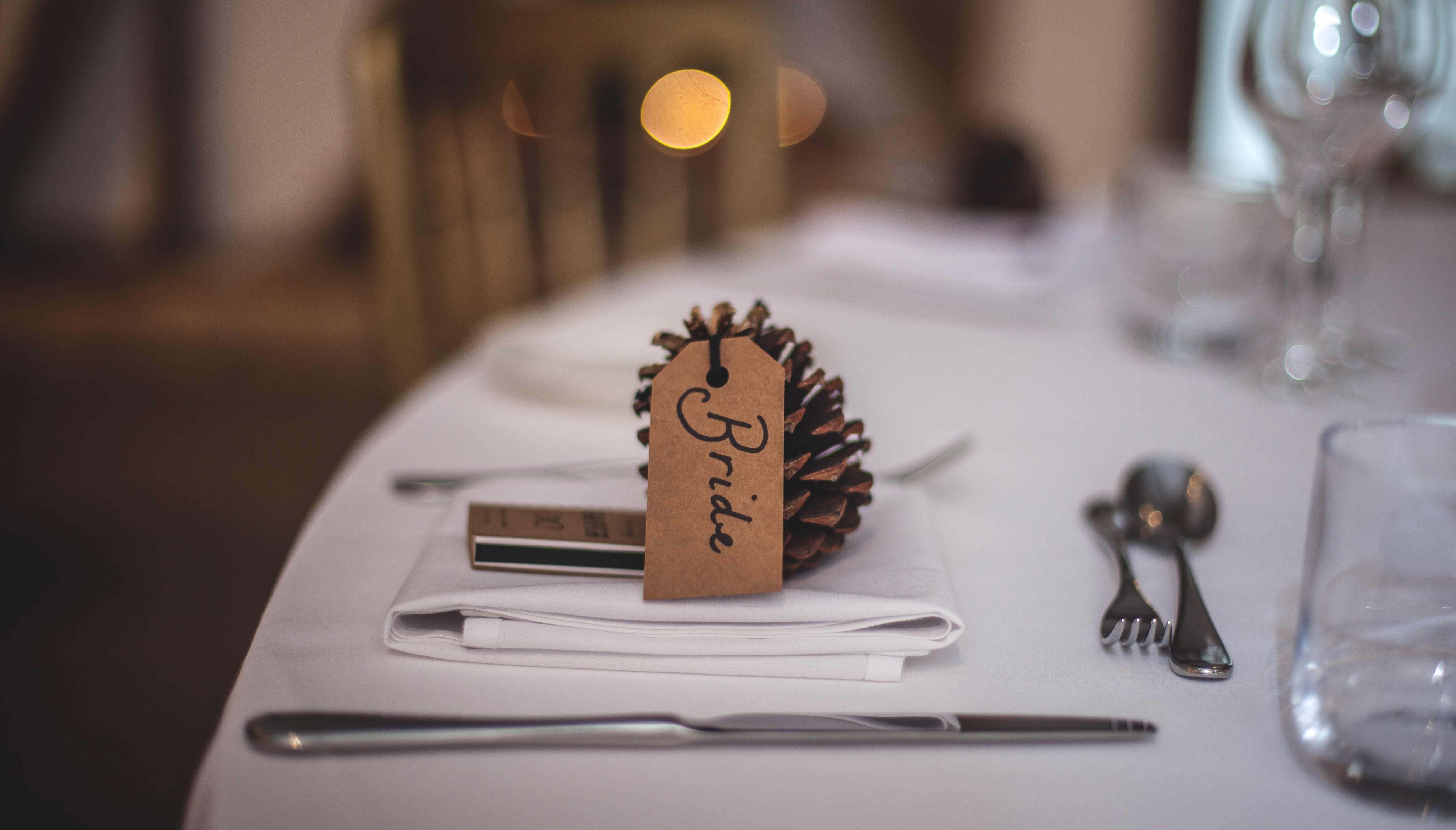 A pine cone with a dining guest's name tag.