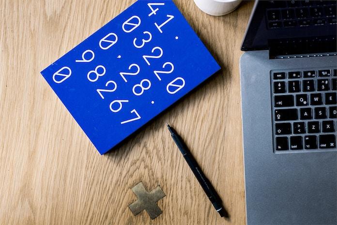 black click pen beside MacBook Pro on table