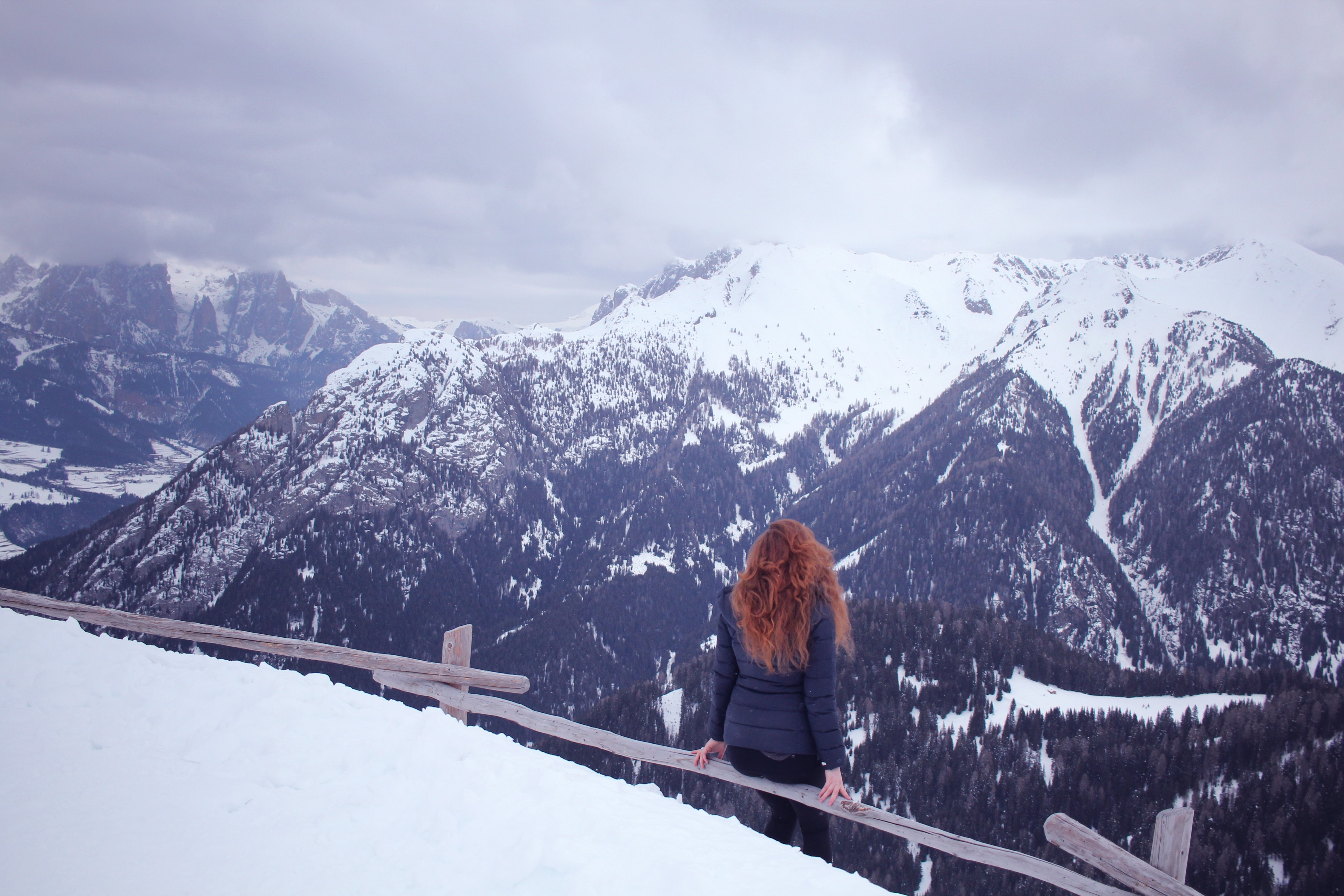 A girl with red hair sits on a fence and is looking at the Dolomite Mountains