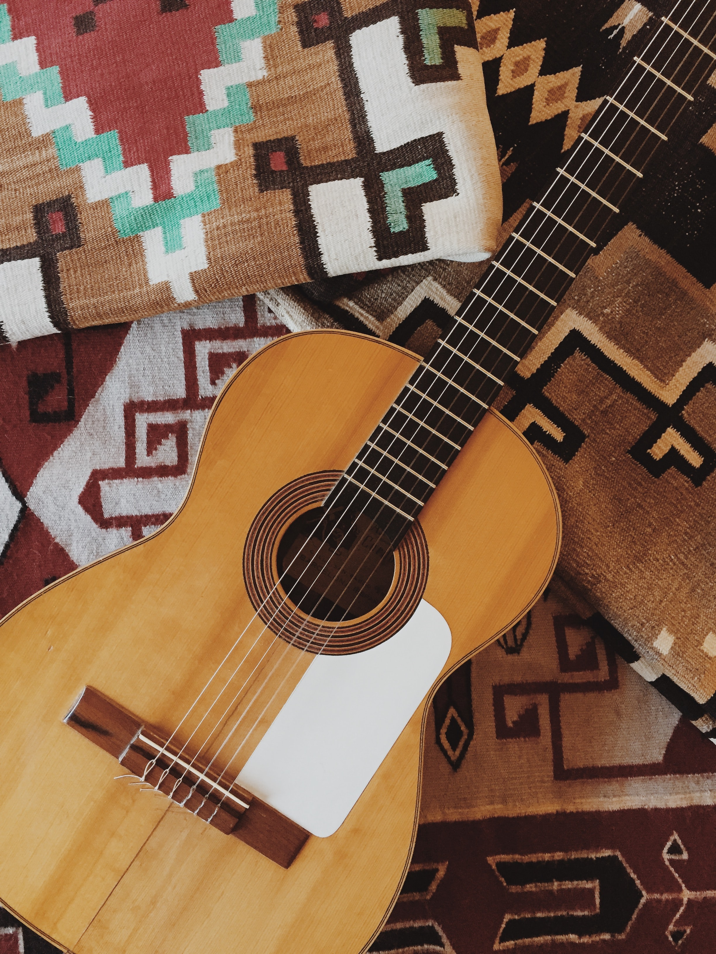 An acoustic guitar and tribal patterned pillows