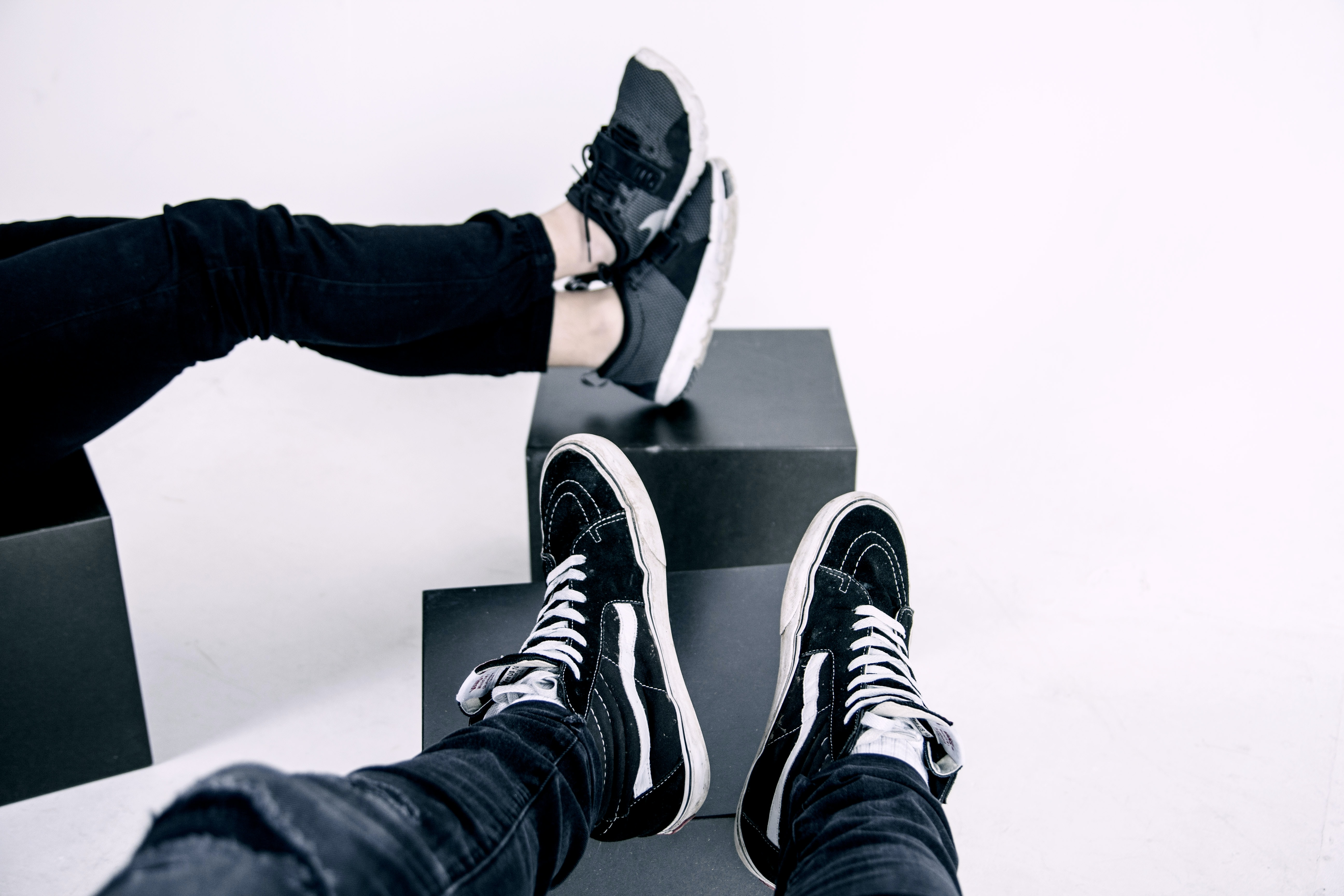Two people in sneakers sitting with their legs on black cubes