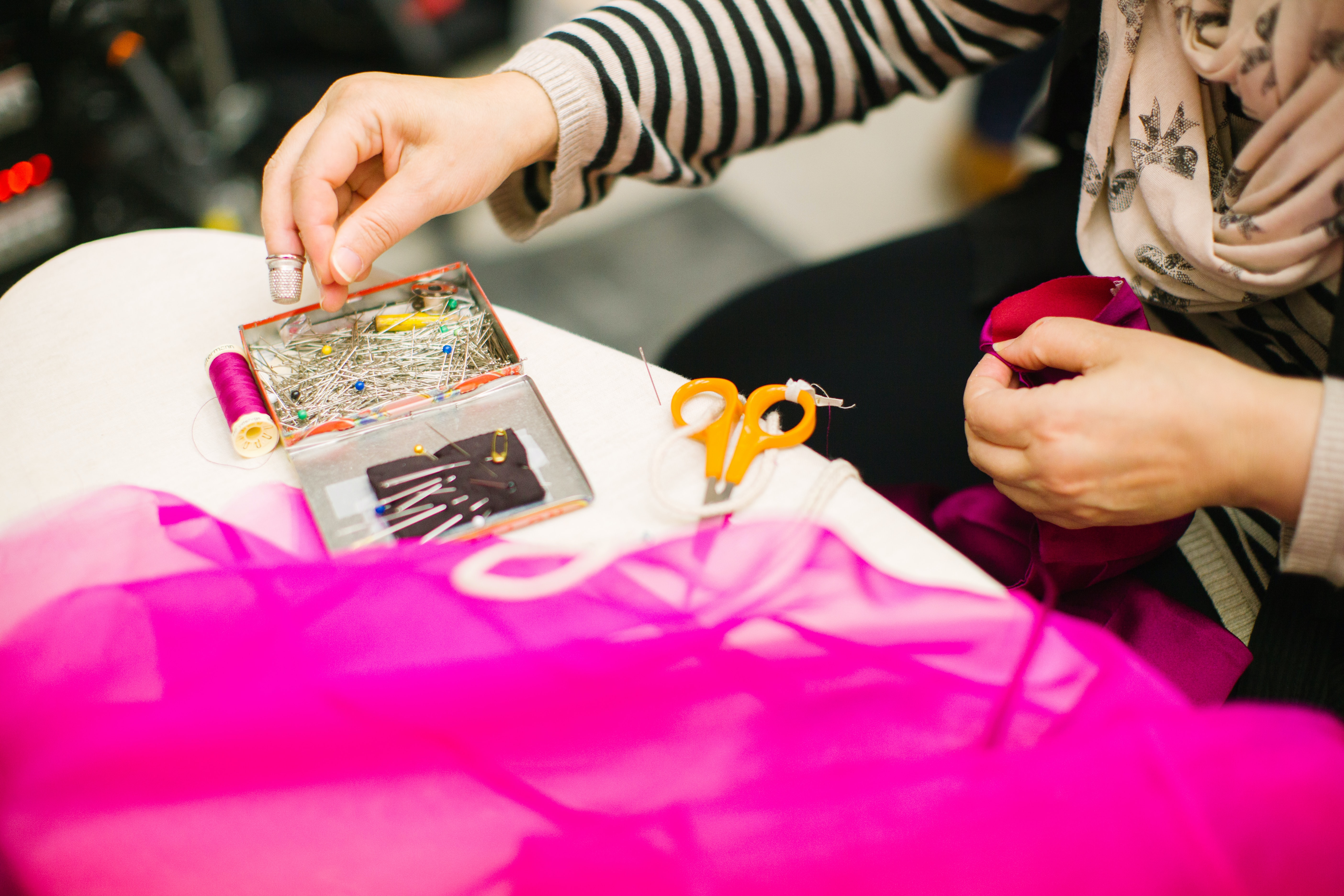 A person reaching for a needle while sewing pink fabric