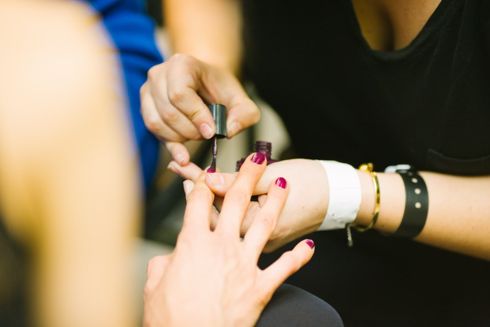 A woman getting her nails painted by a beautician.