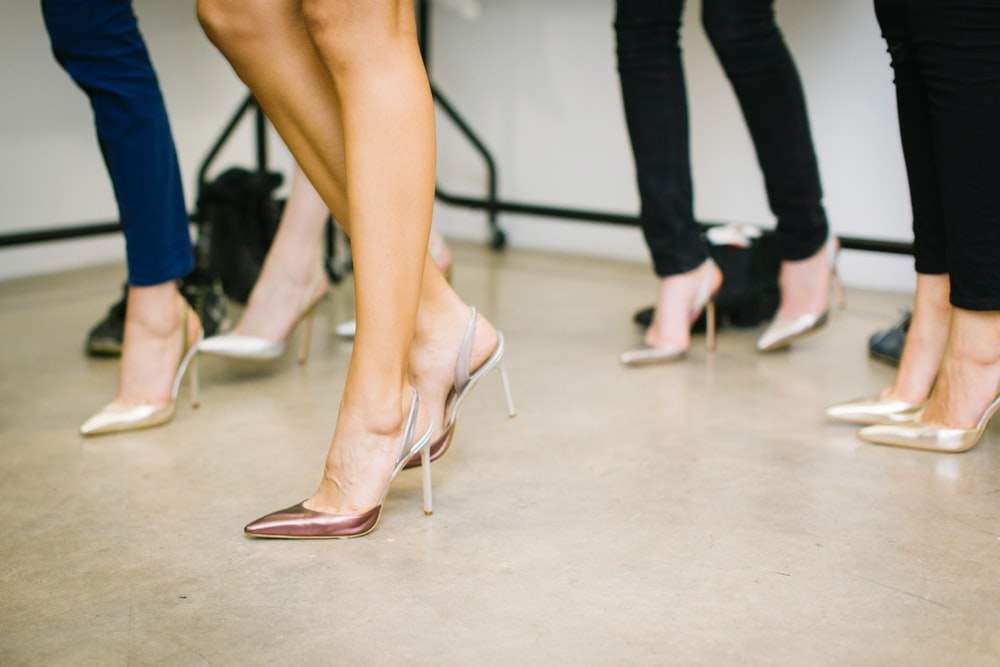 four woman wearing assorted heels