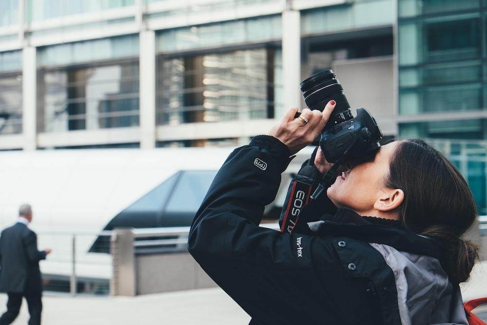 woman wearing gray and black jacket using DSLR camera