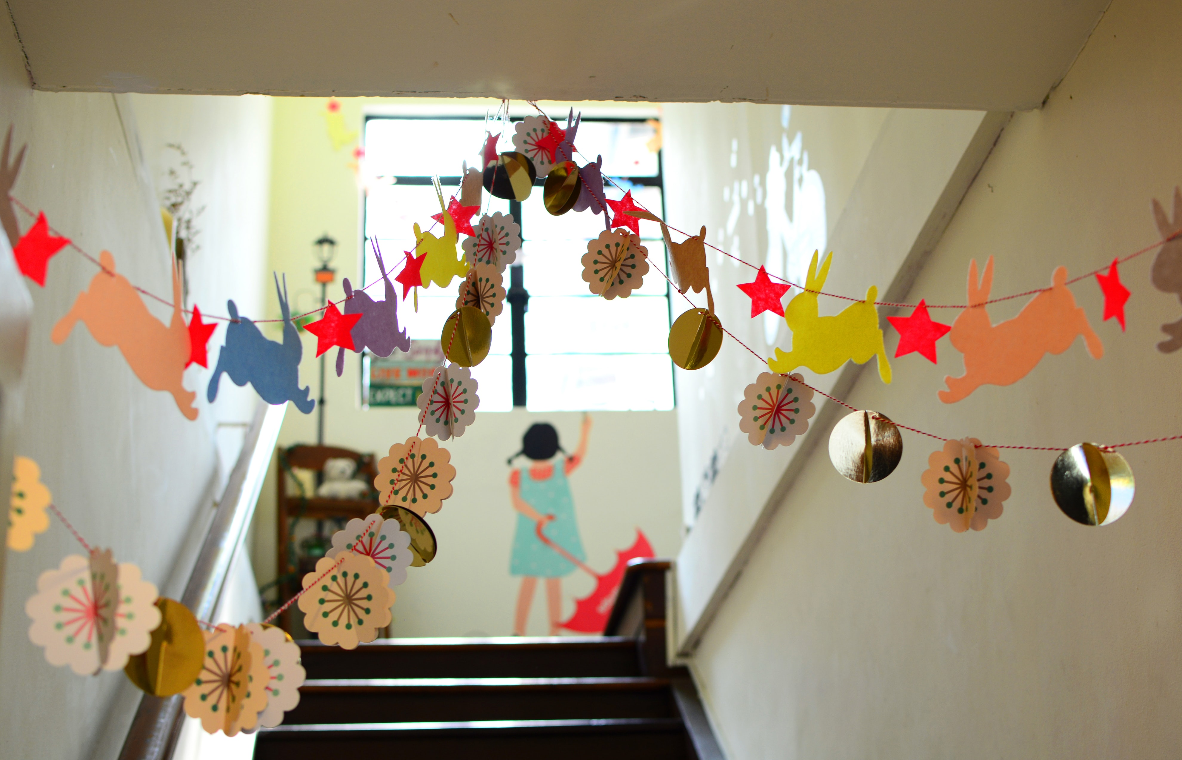 A school hallway decorated with bunnies, stars, and polka dots with a girl holding an umbrella painted on the wall in Singapore