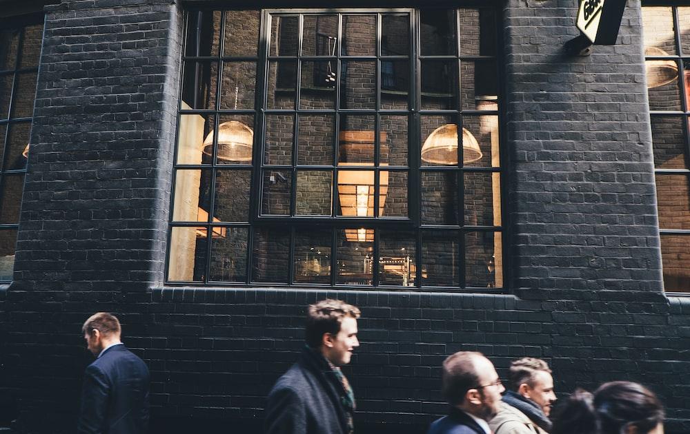 people standing beside black building