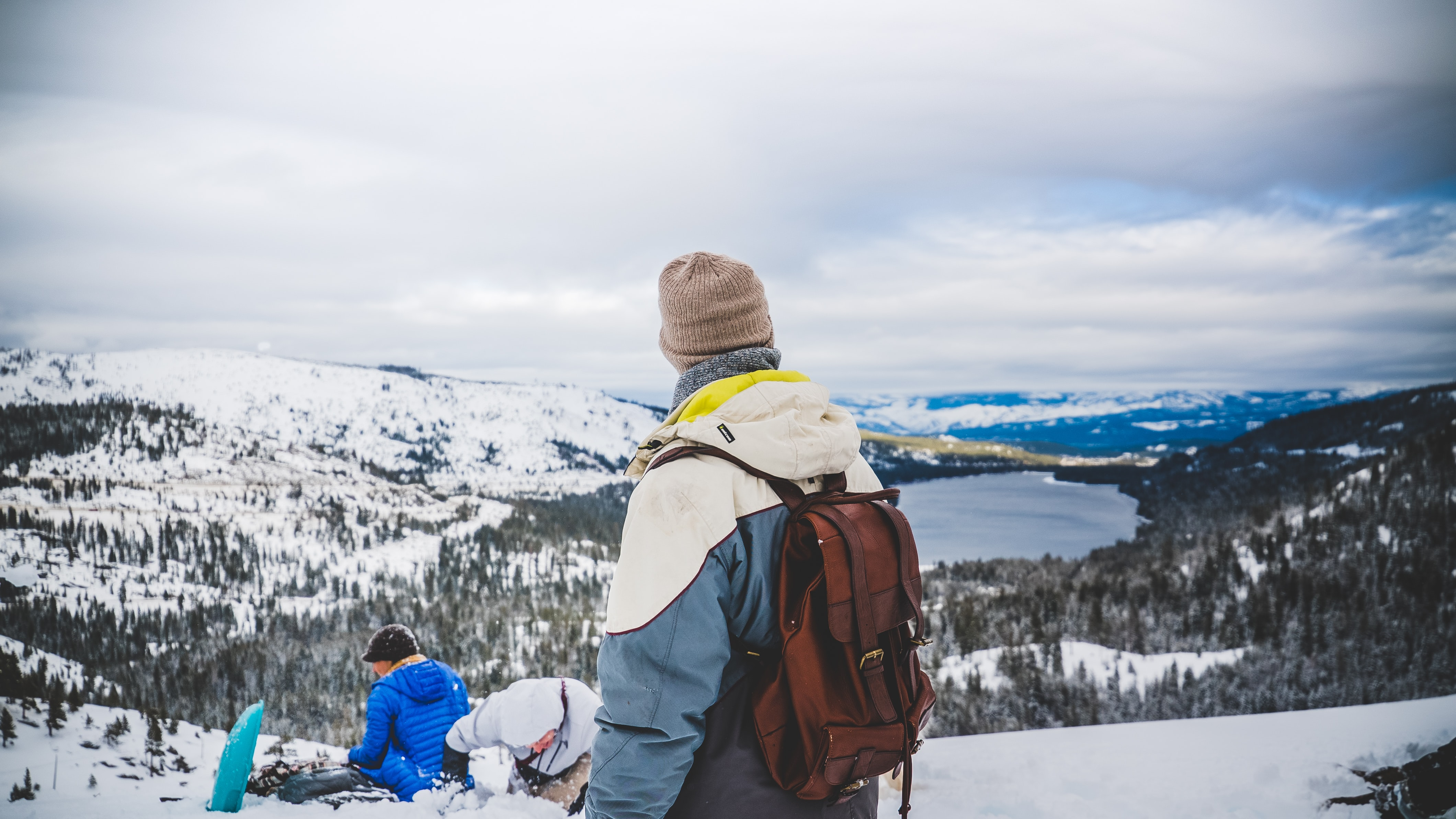 A backpacker in a beanie and a jacket looking at a snowy mountain valley with two people in the snow on his side