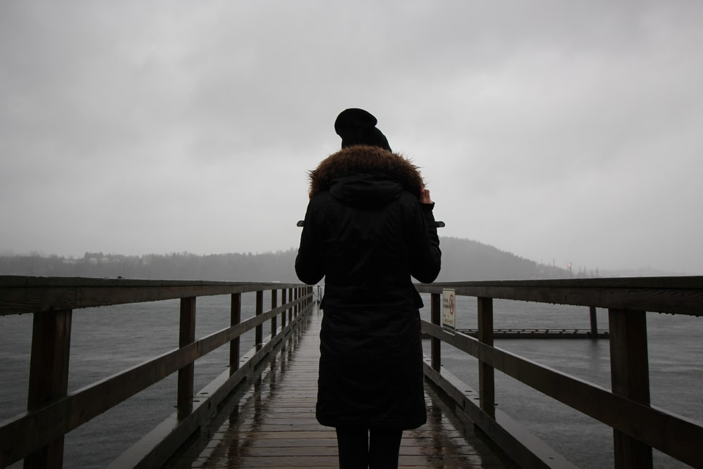 woman on dock near lake