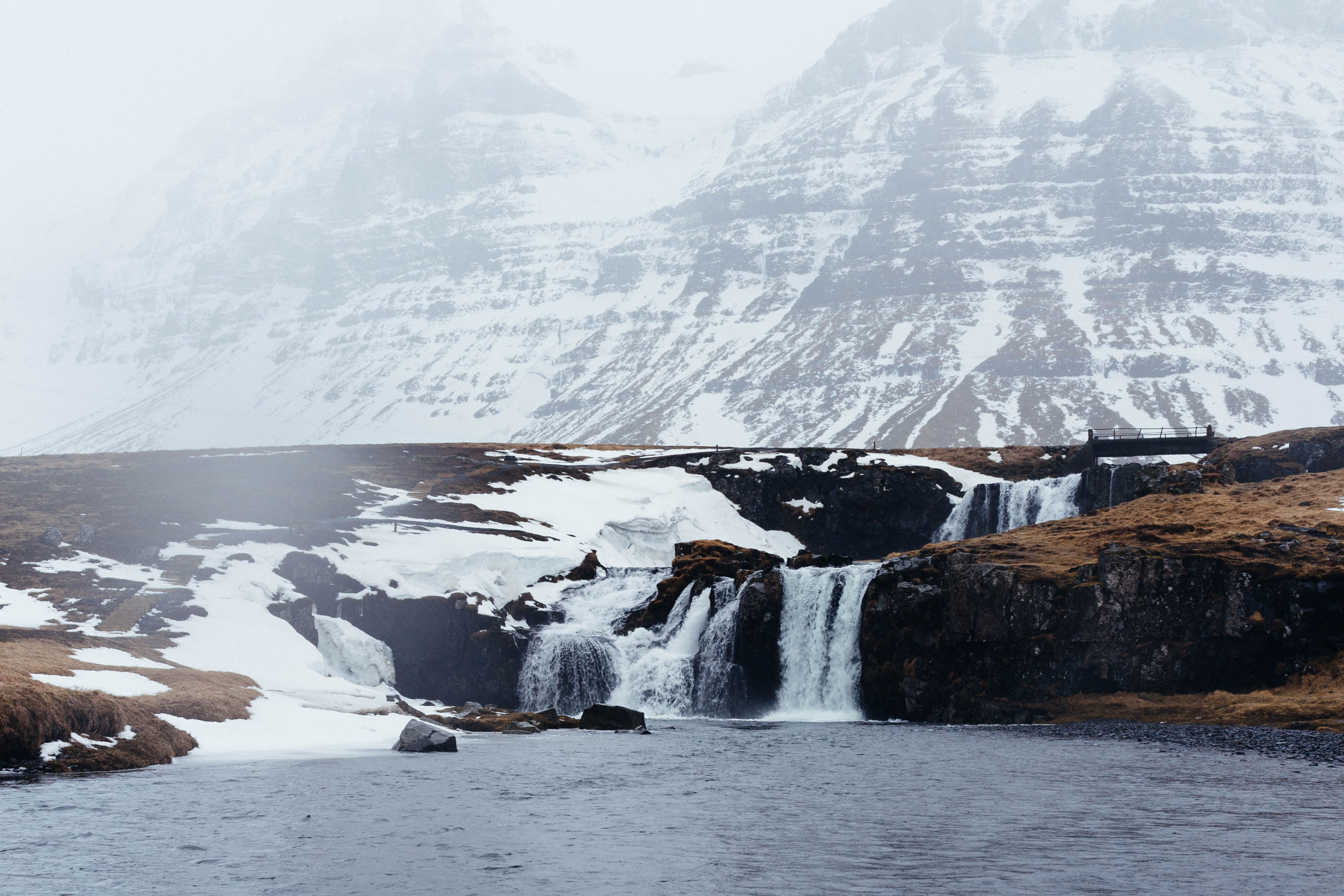 Small waterfalls feed into a lake at the foot of a snowy mountain