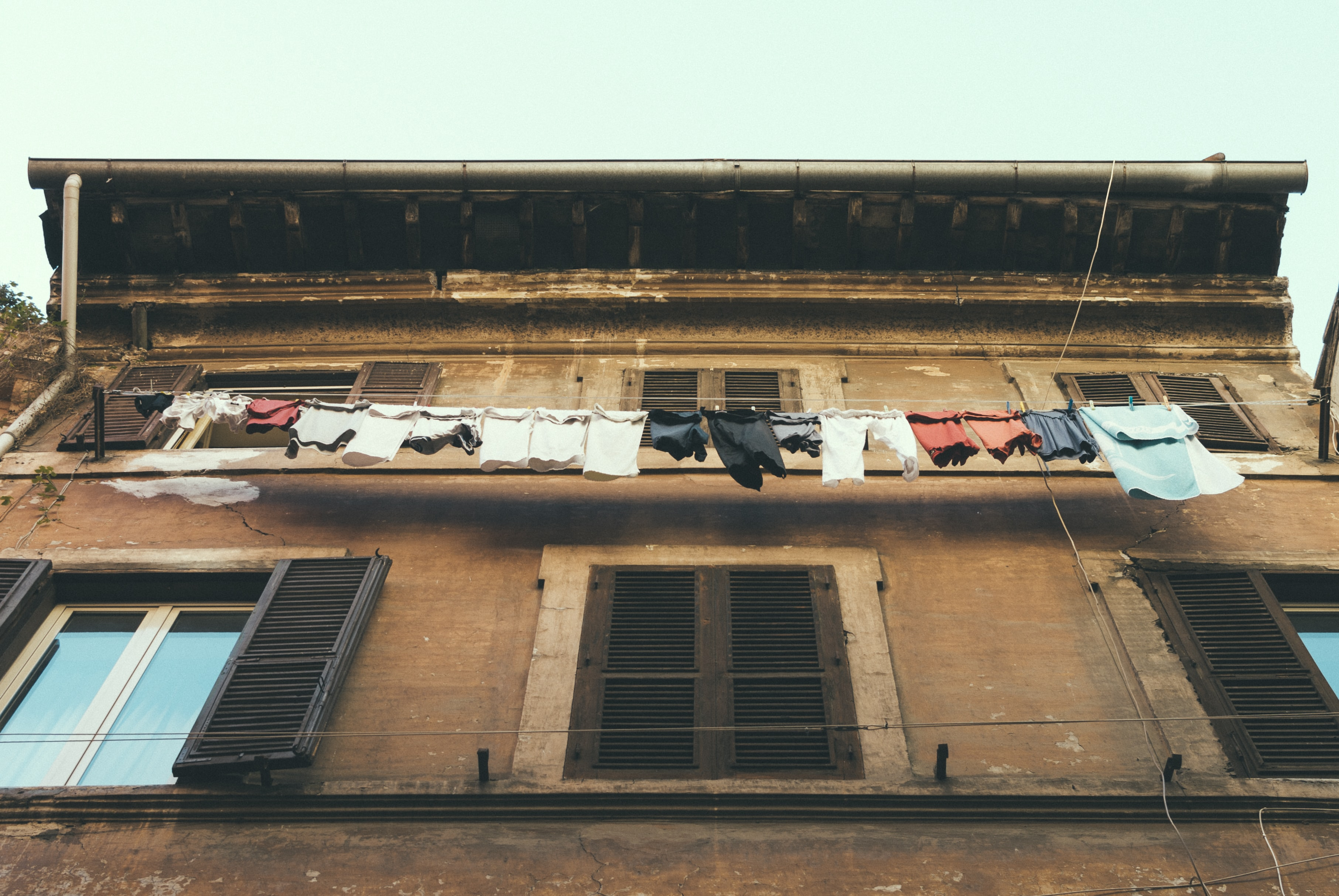 Clothes are drying on a long clothesline at an old building with wooden window shutters.