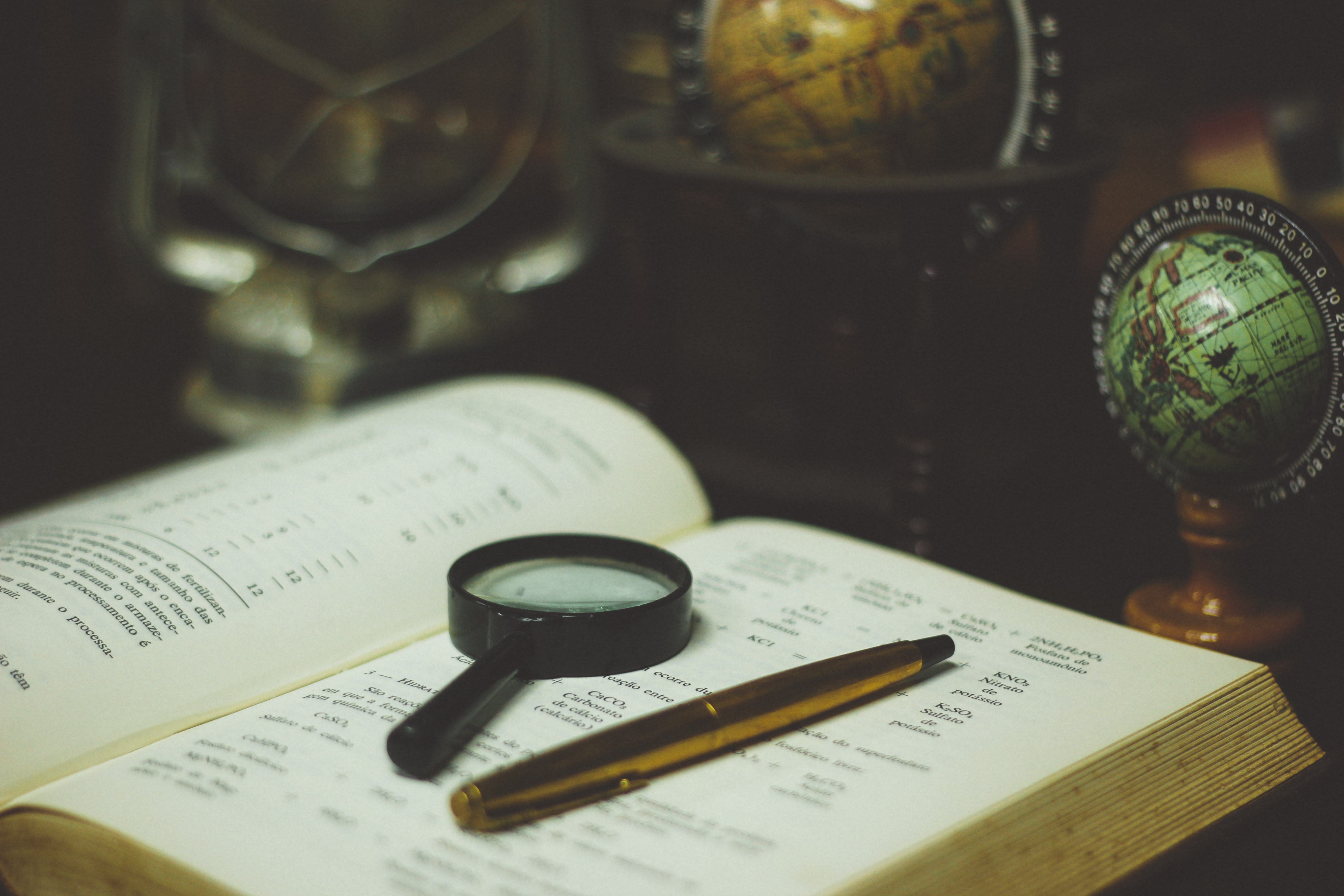 A book with a magnifying glass on top of it, next to a pen, and globes on a desk in Cianorte