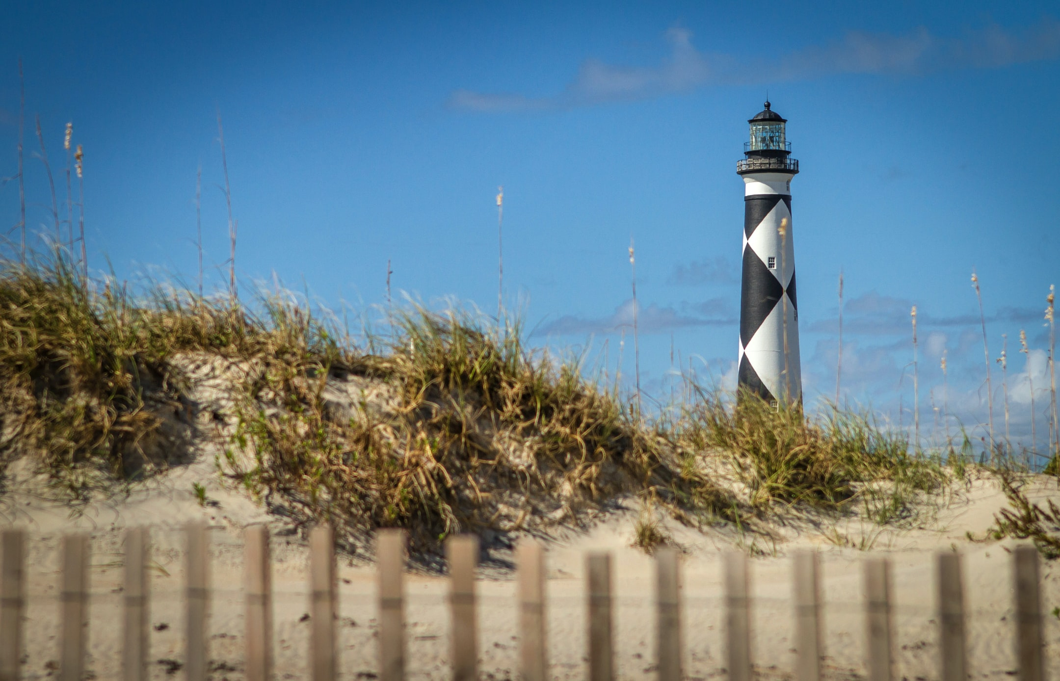 Wooden fence by a sand dune with a black and white lighthouse in the background at Cape Lookout