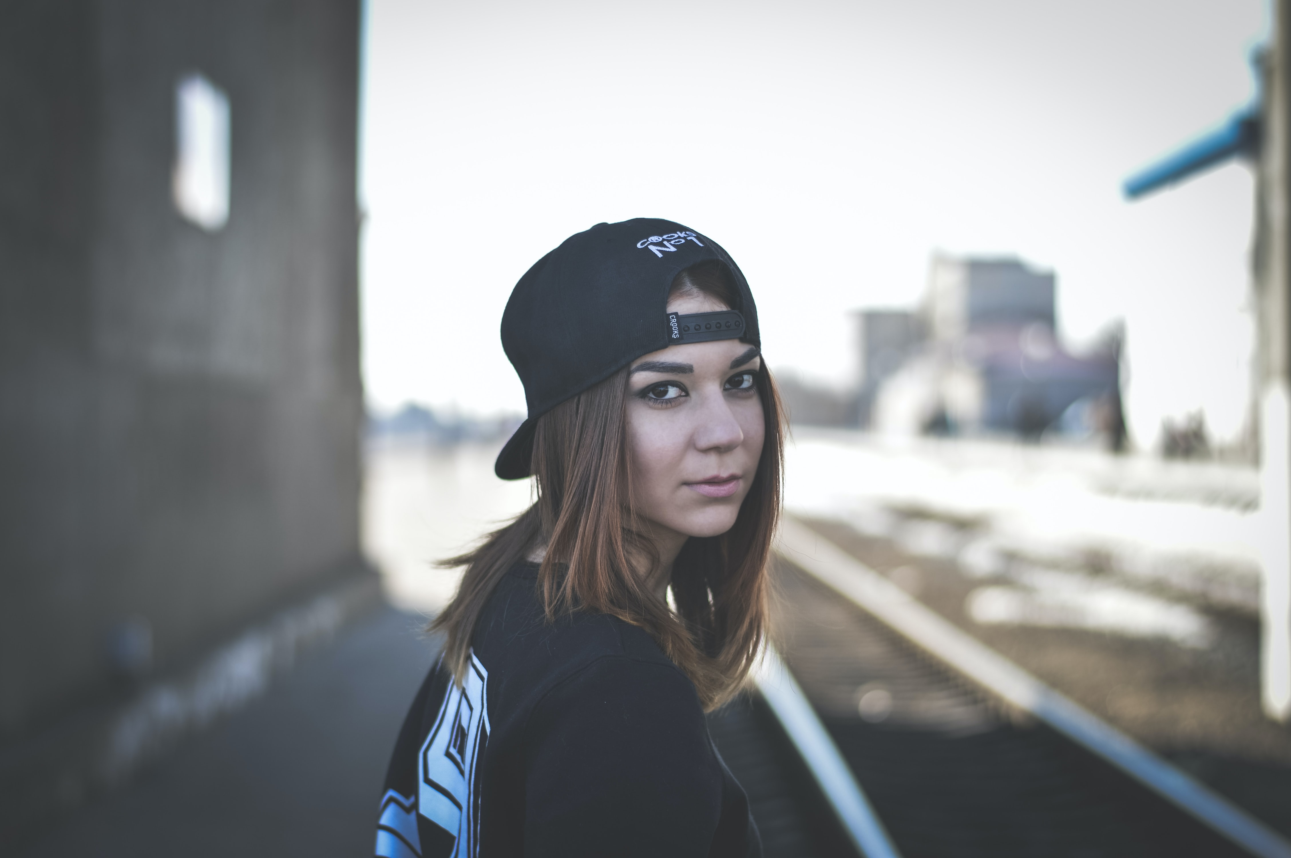 Woman in urban streetwear looks back at the camera seriously